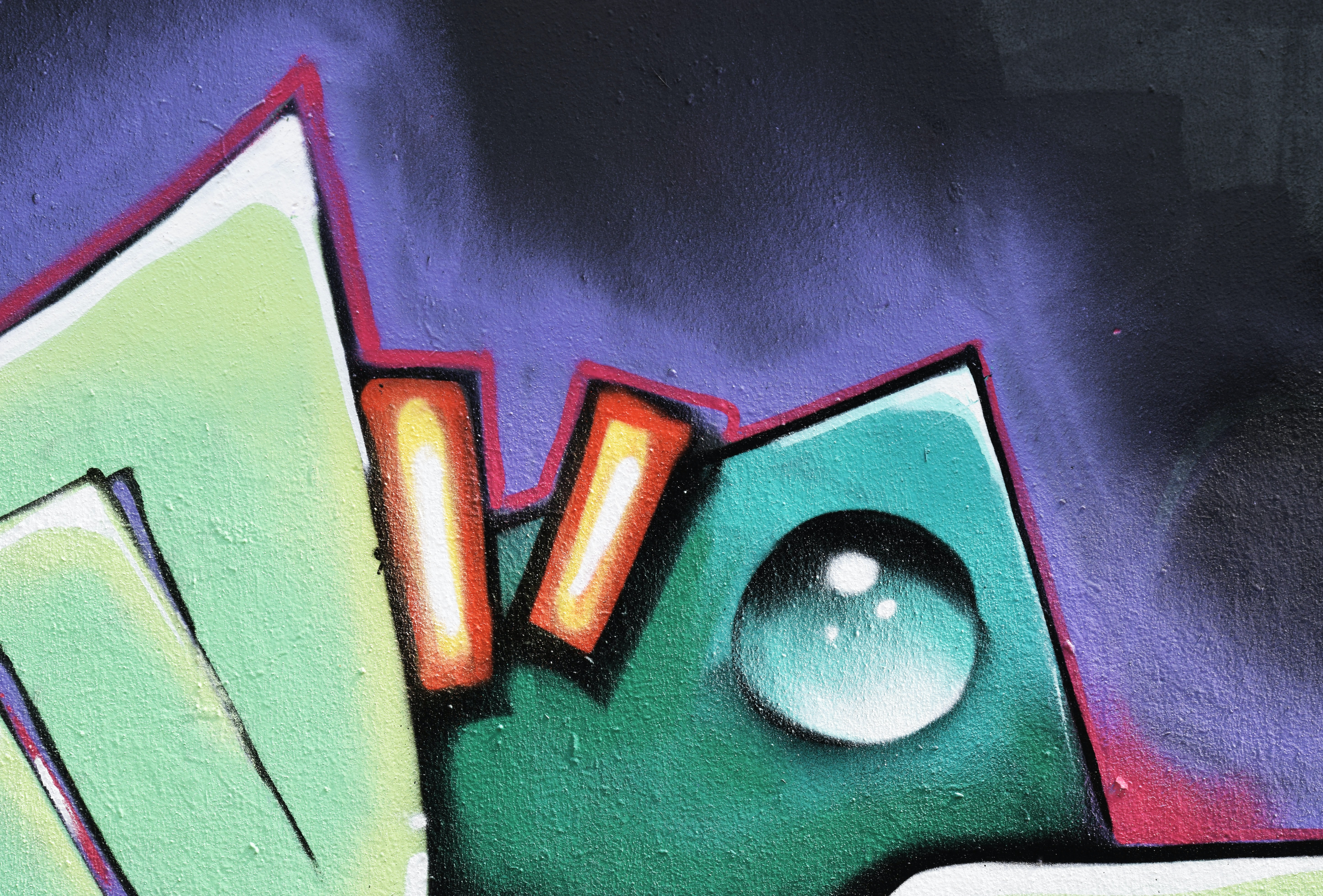 Close up of green, purple and red graffiti street art mural