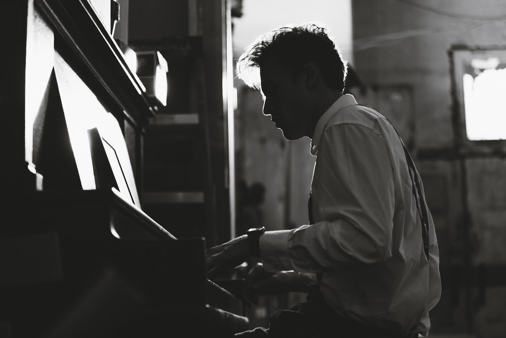 grayscale photography man playing piano