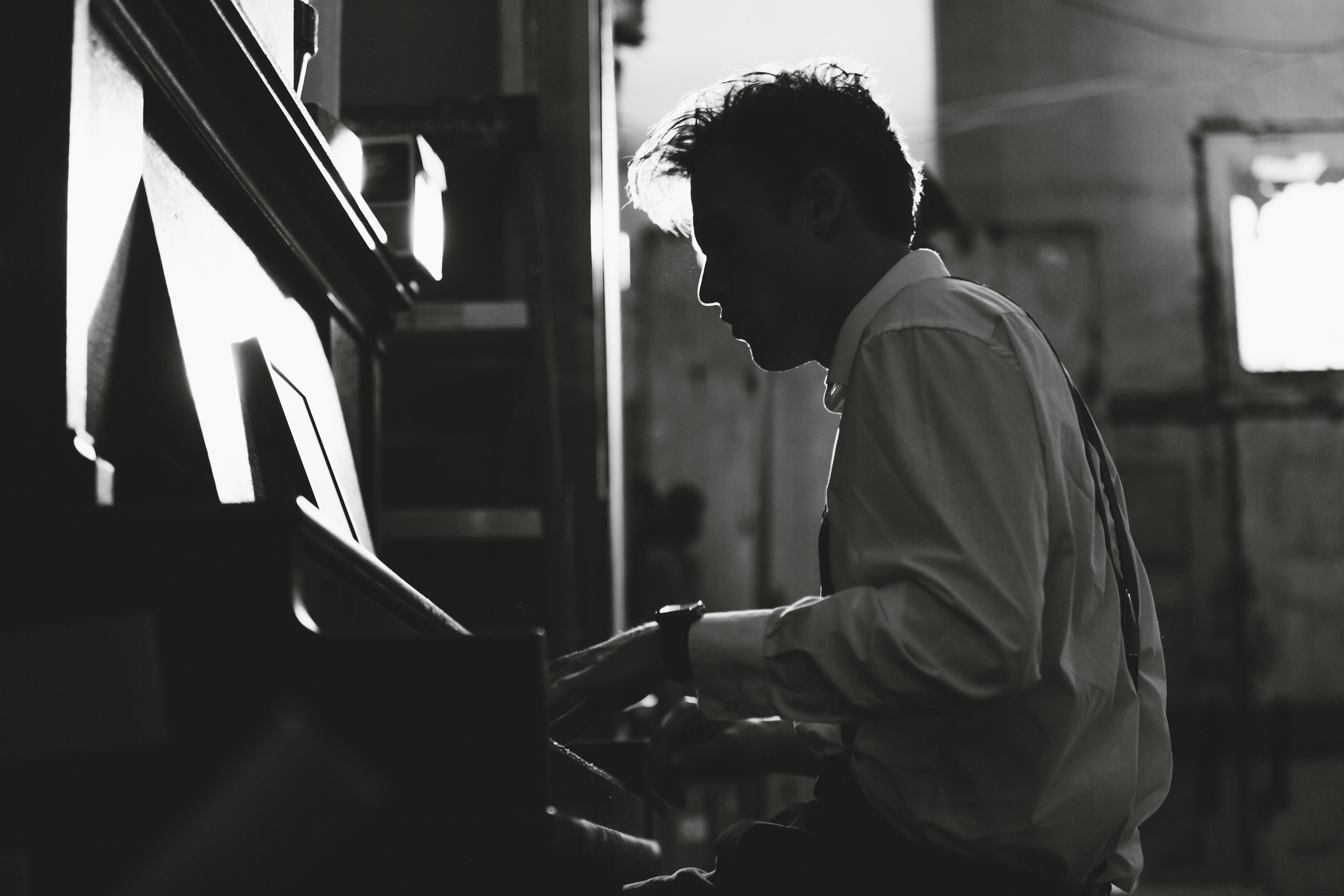 A black-and-white shot of a man in a white shirt playing the piano