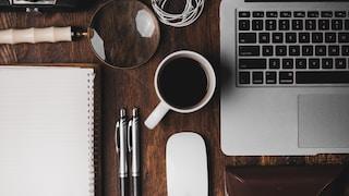cup of coffee near MacBook Pro