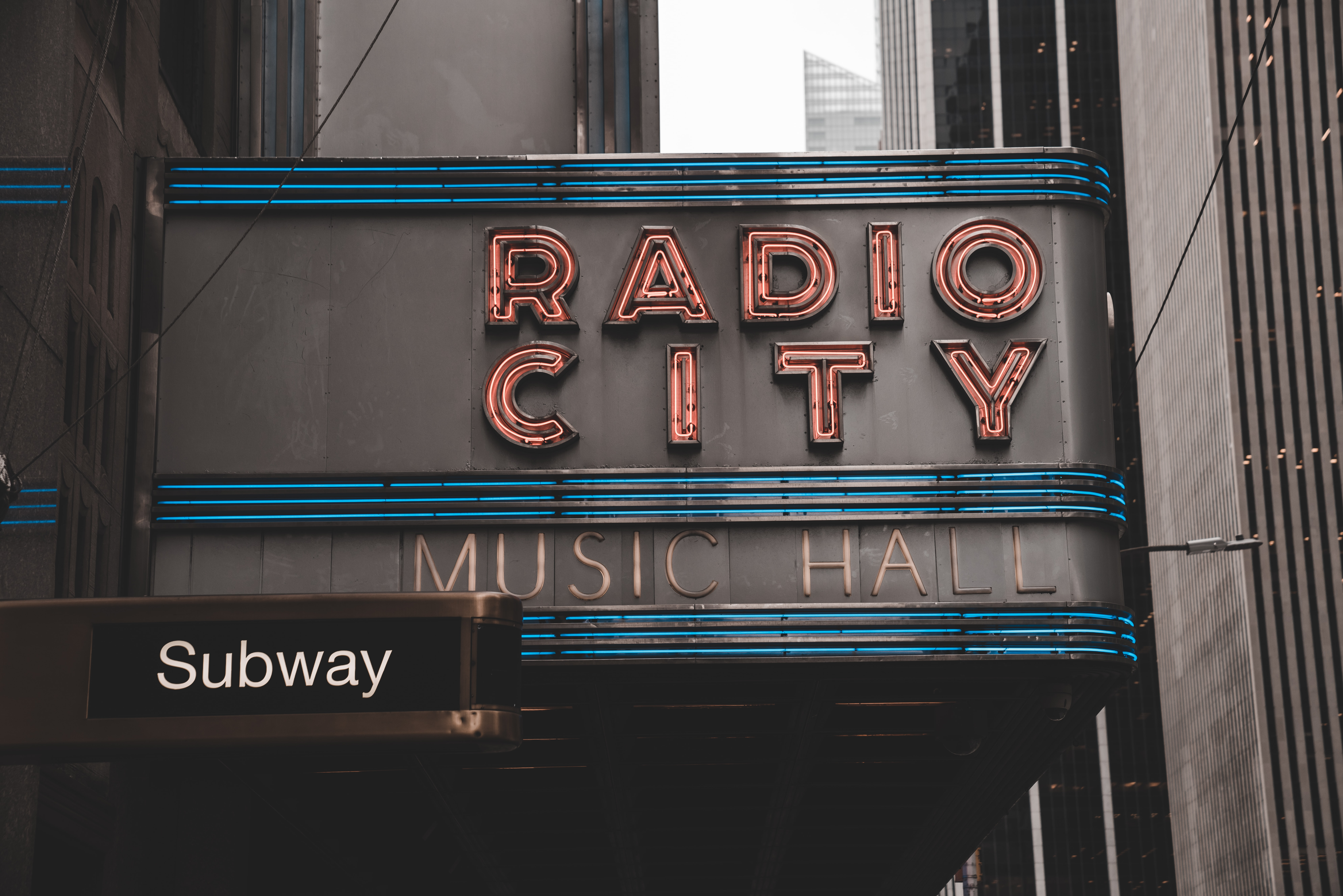 """A neon reads """"Radio City Music Hall"""" next to a subway station in daylight"""