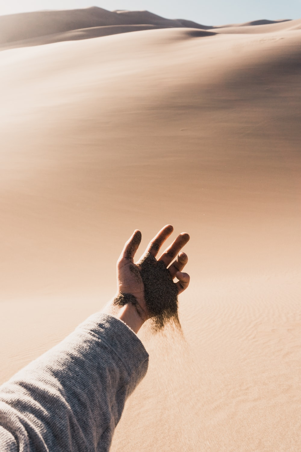 person dropping sand from his hand during daytinme