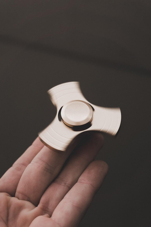 person holding brown 3-blade fidget spinner