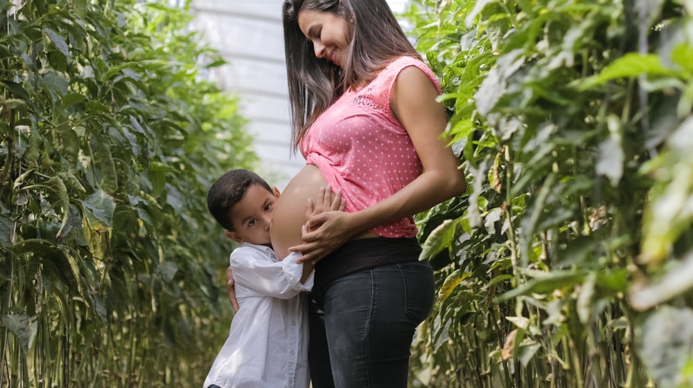 pregnant woman and child standing outdoor
