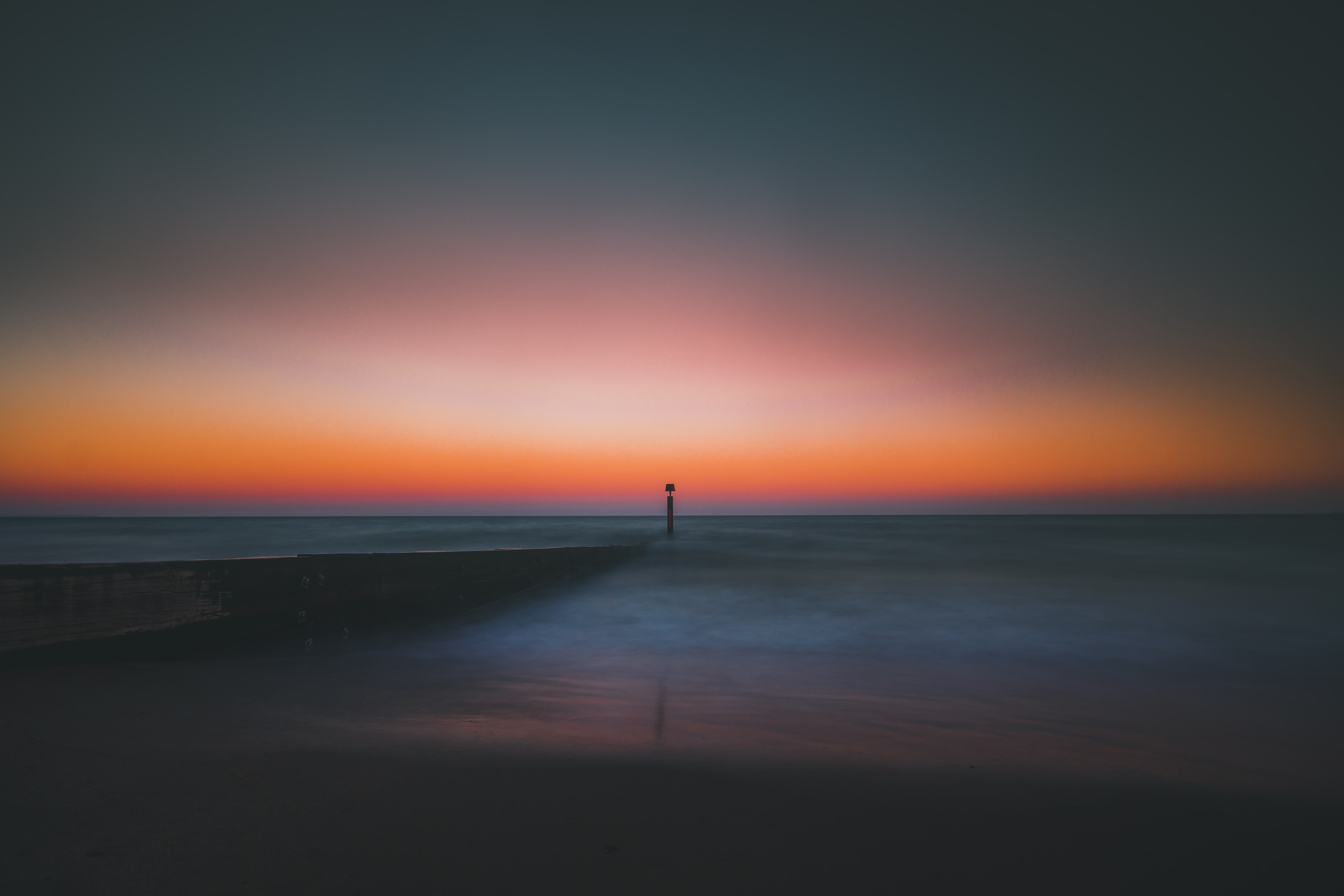 One silhouette pole in the calm, smooth sea at Bournemouth beach during sunrise-or-sunset coloring the dark sky orange