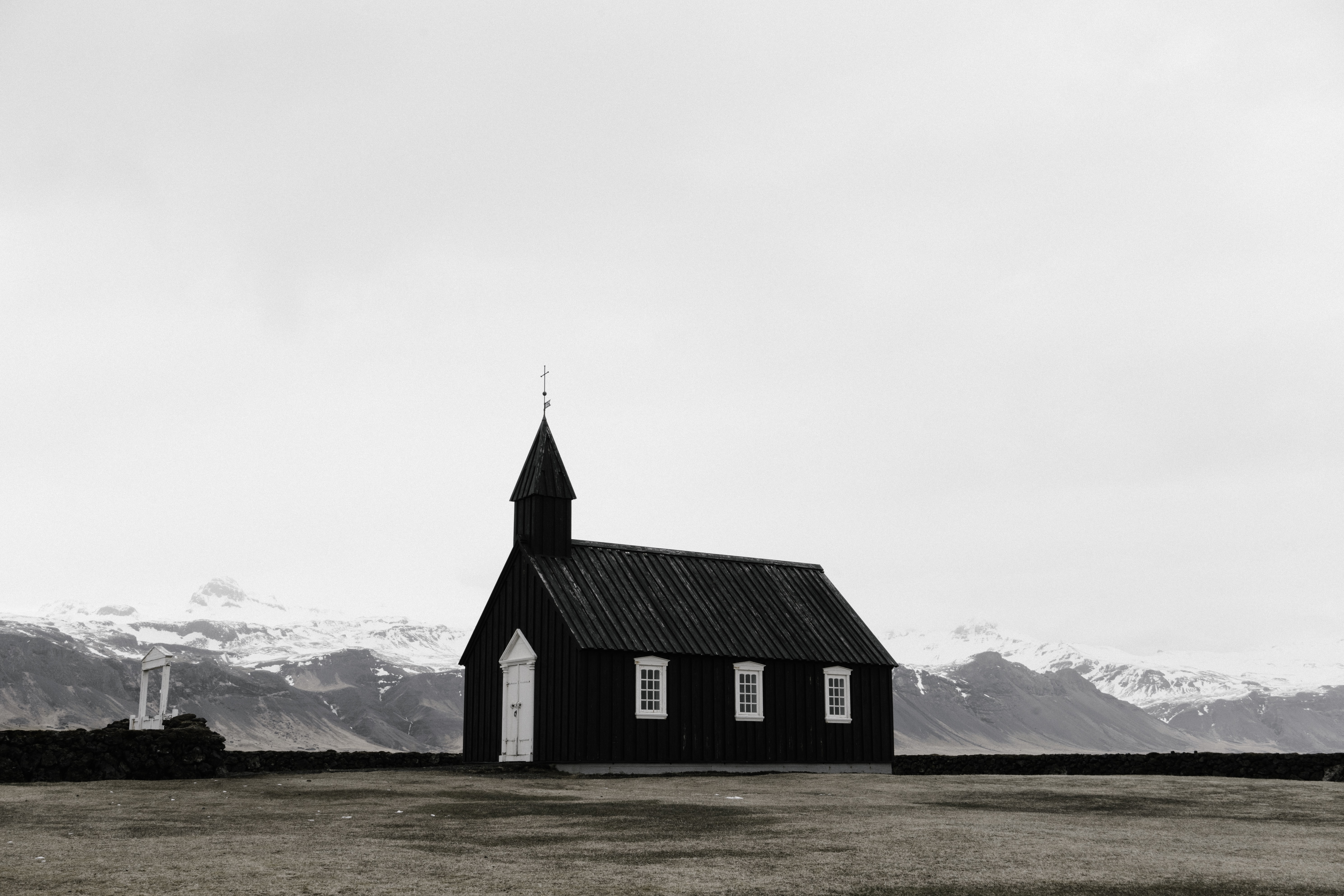 A small chapel in a plain with snowy mountains on the horizon