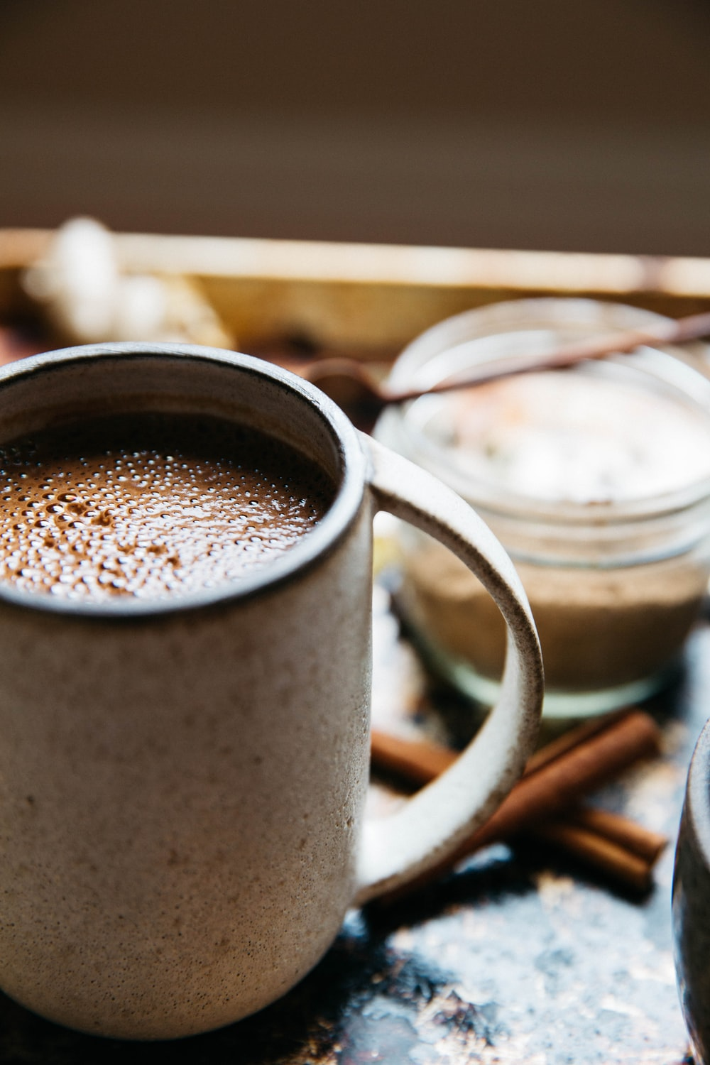 beige mug with hot chocolate near cinnamon sticks on surface