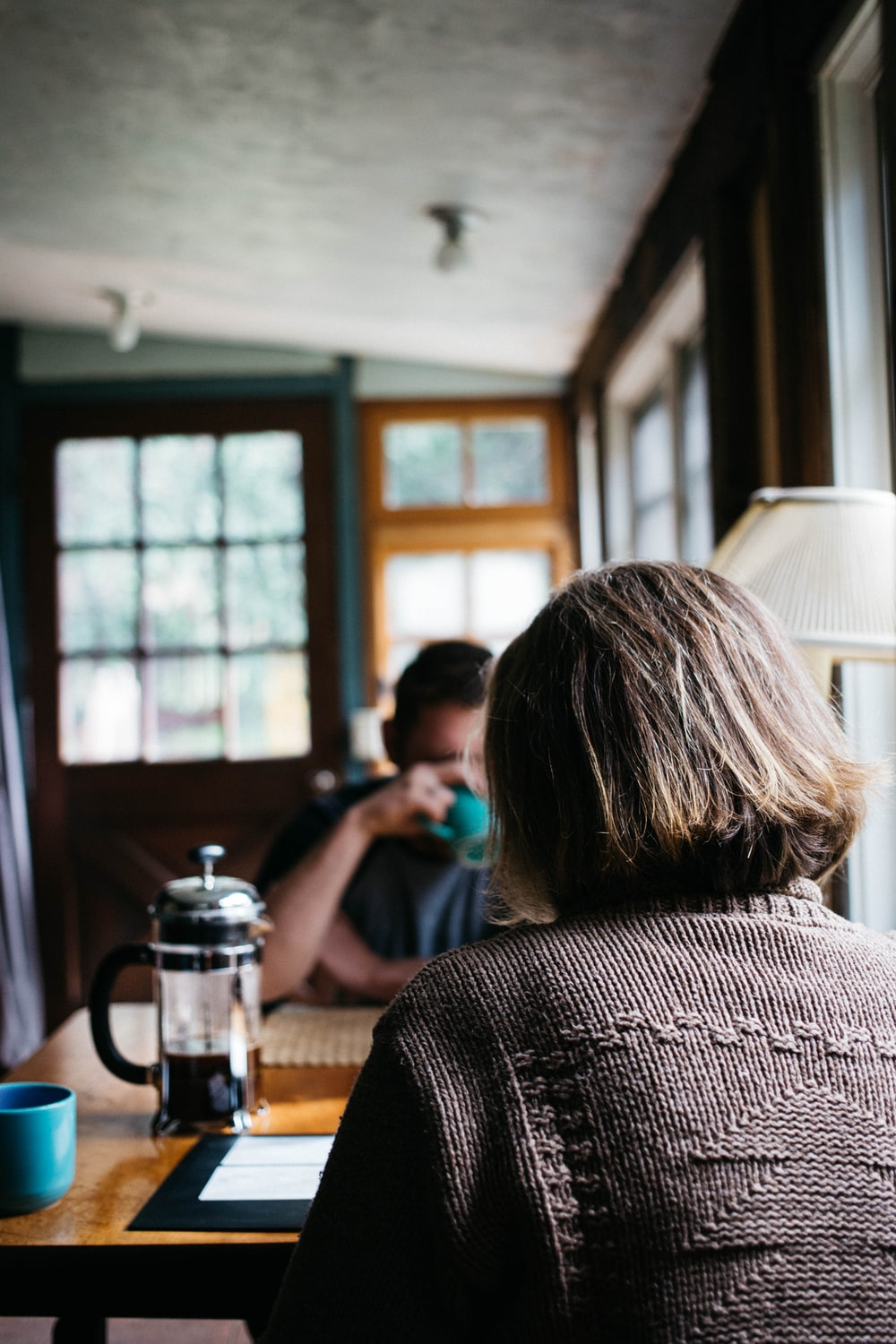A woman and man sit across a cafe table with mugs and a french press