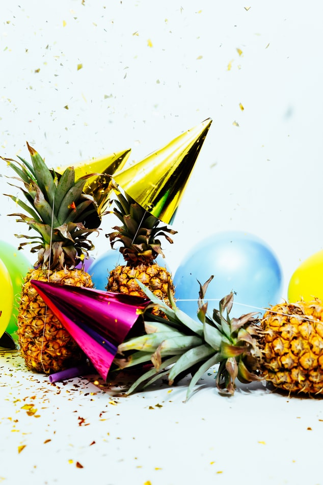 A photo of a few pineapples wearing party hats, one is tipped over and there is confetti.