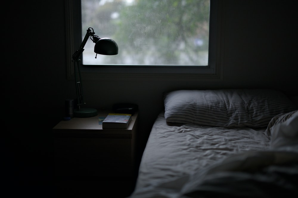 photo of bed near task lamp