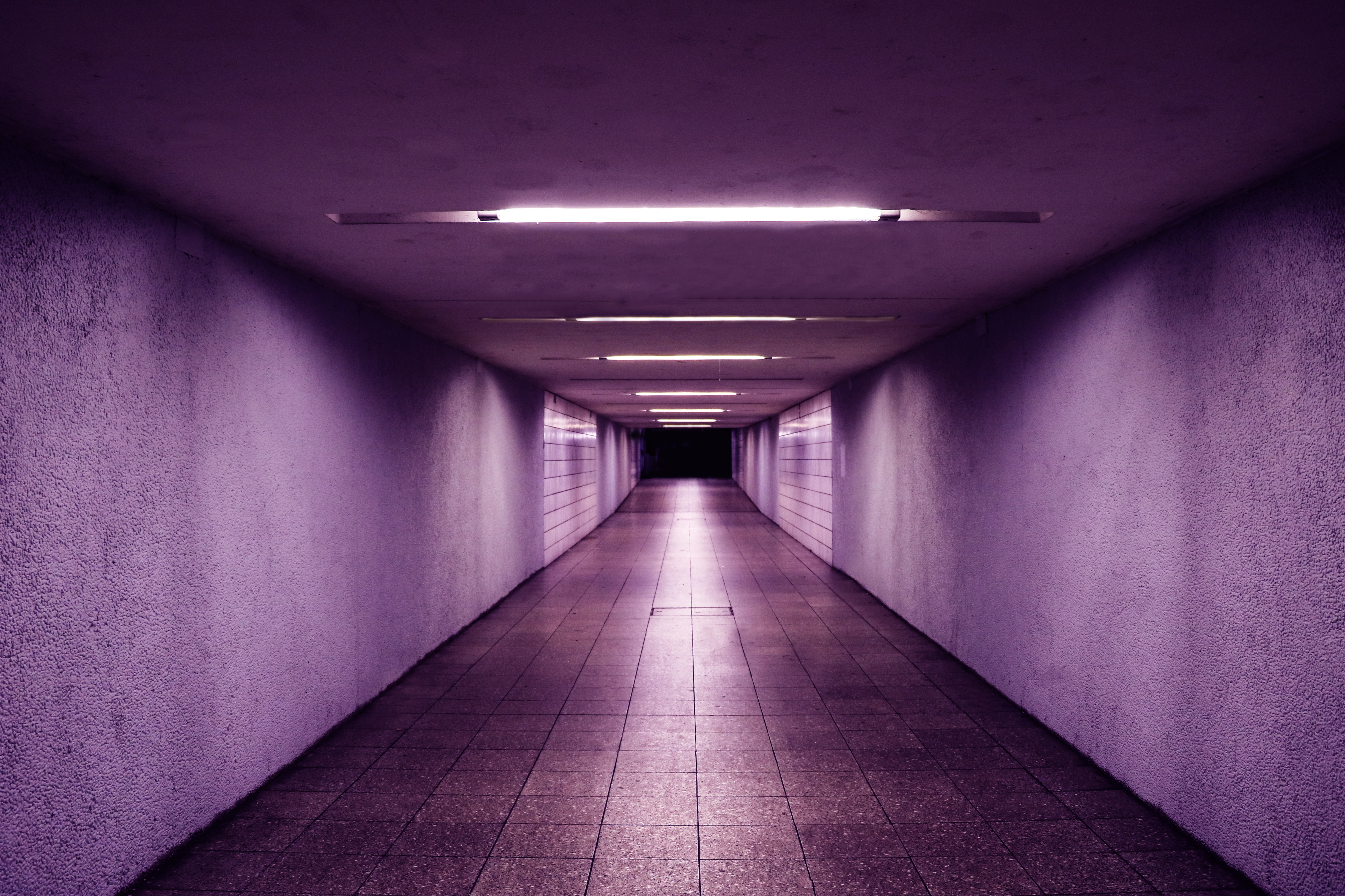 Empty underpass with purple lighting leading to a dark corridor