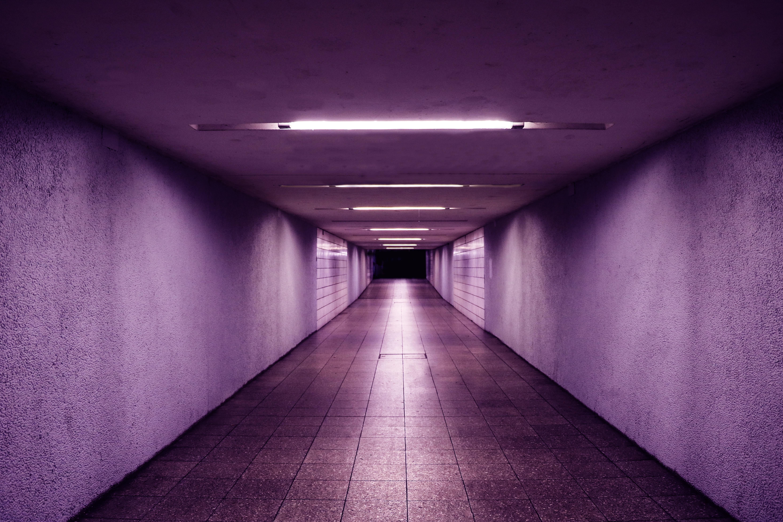 Empty underpass with purple lighting leading to a dark corridor