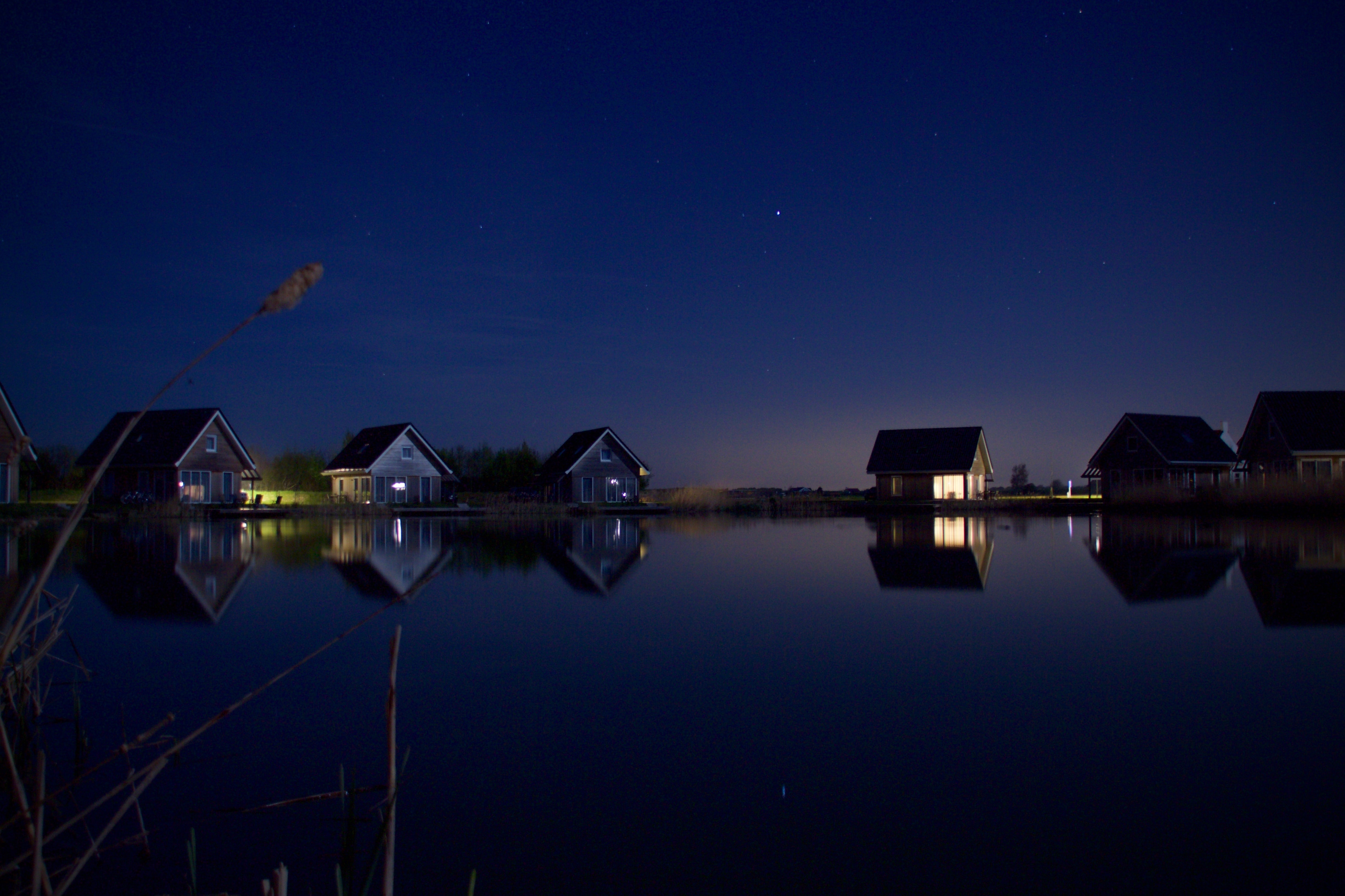 calm body of water near six houses and trees at night