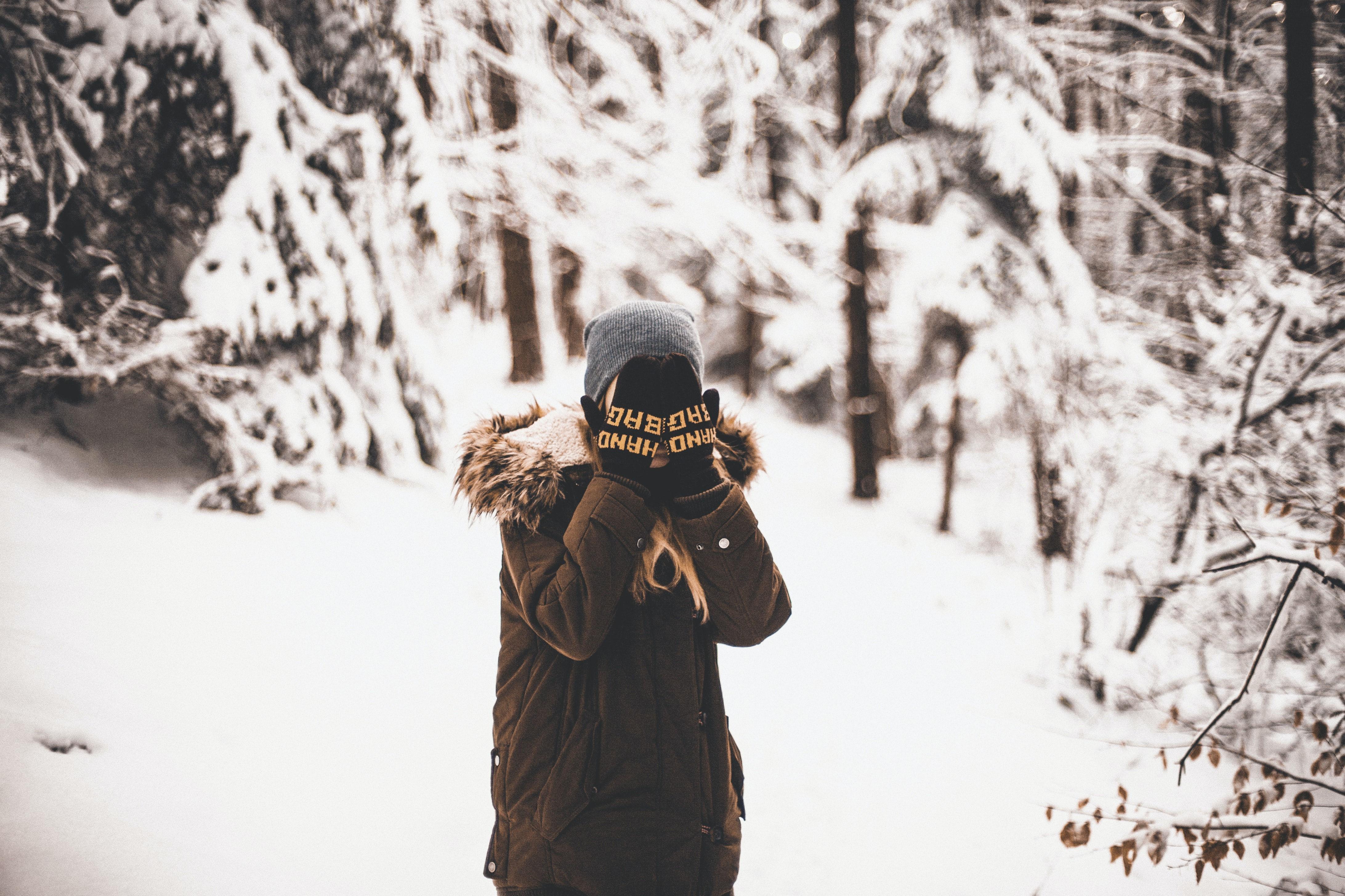 A woman in a forest covered in snow is wearing gloves, a jacket and a hood