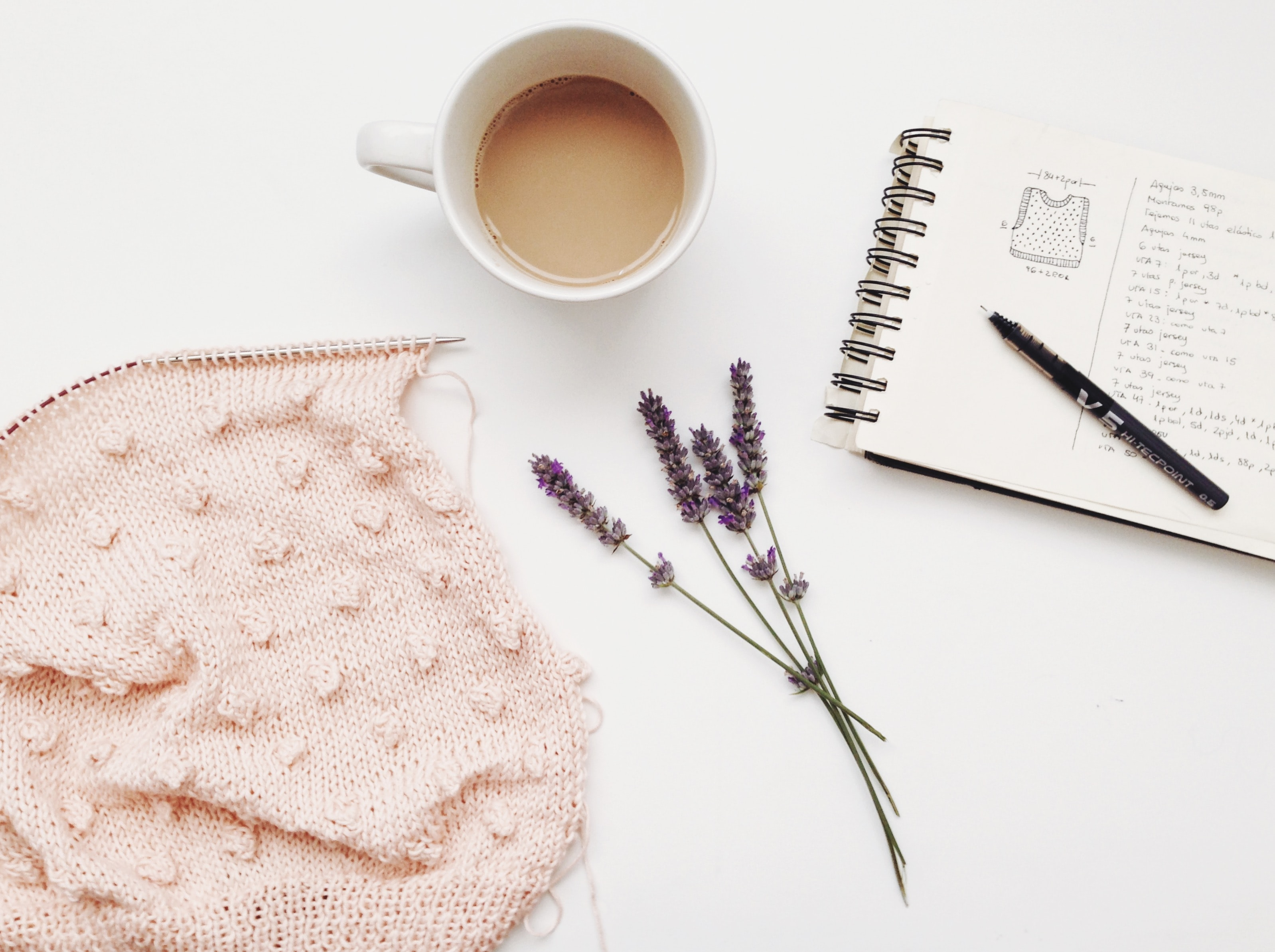 A bunch of lavender flowers next to a cup of coffee and a notepad on a white surface