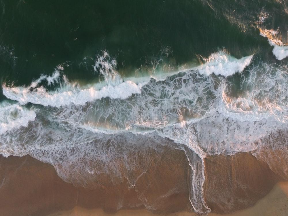 body of water splashing on a sand