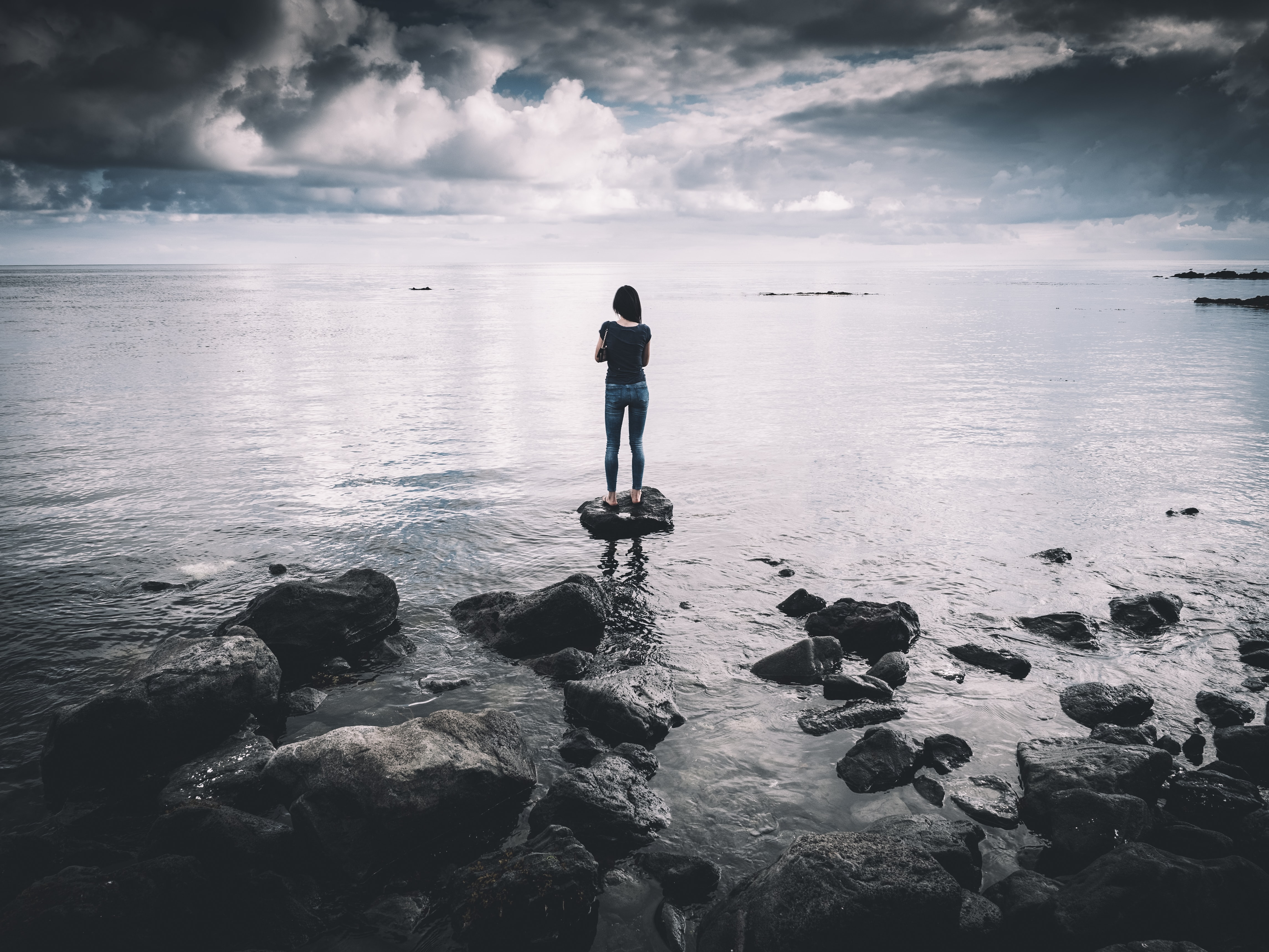 woman standing on rock surrounded with body of water