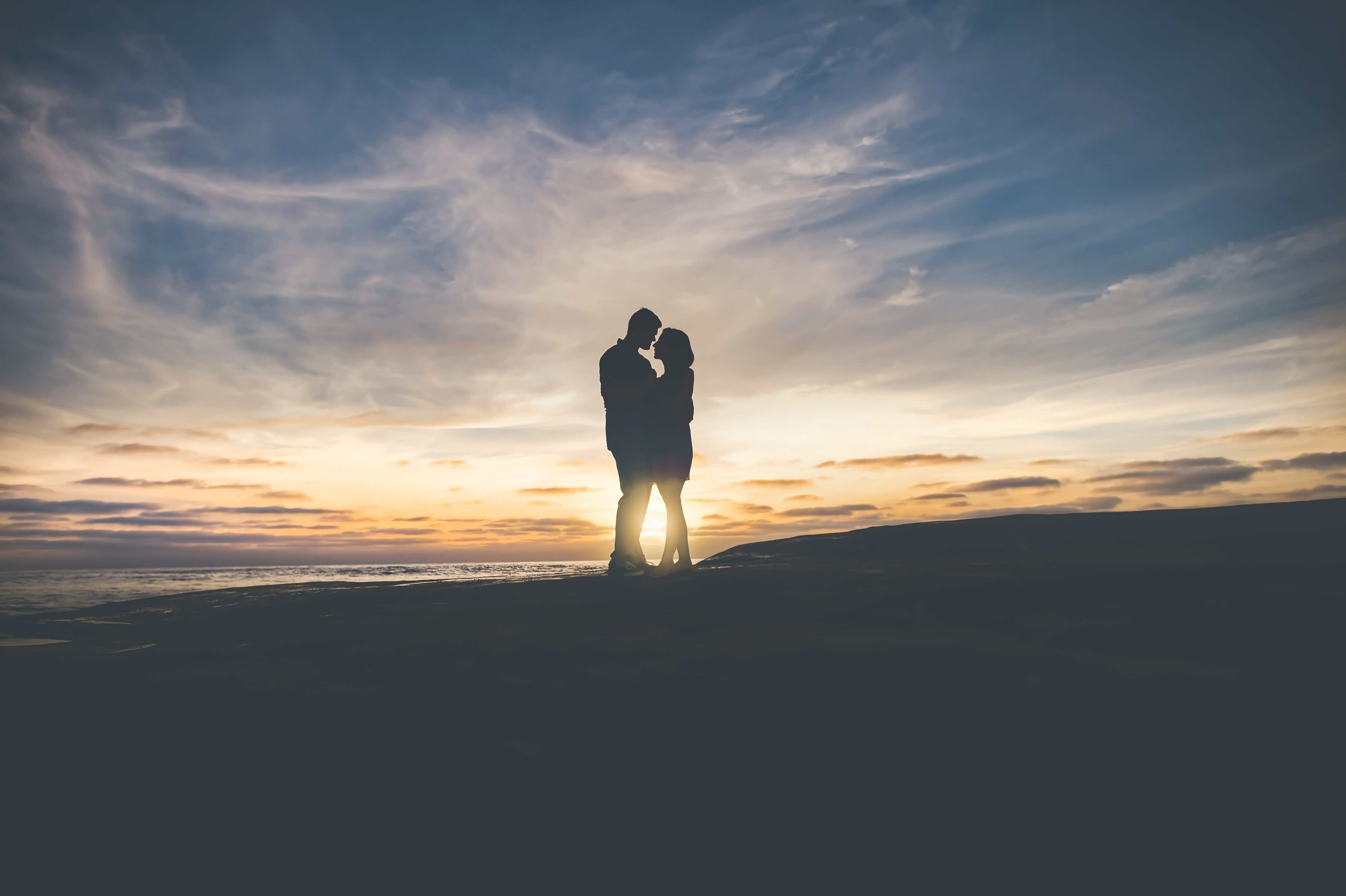 Beach scene of a young couple silhouetted against a sunset sky