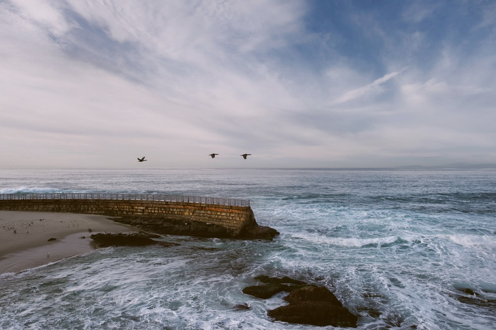 brown concrete fence beside sea waves under white clouds at daytime