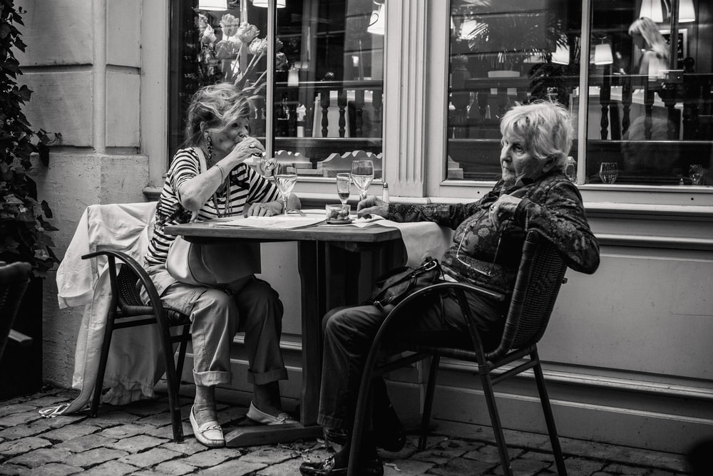 grayscale photo of two woman sitting beside the table
