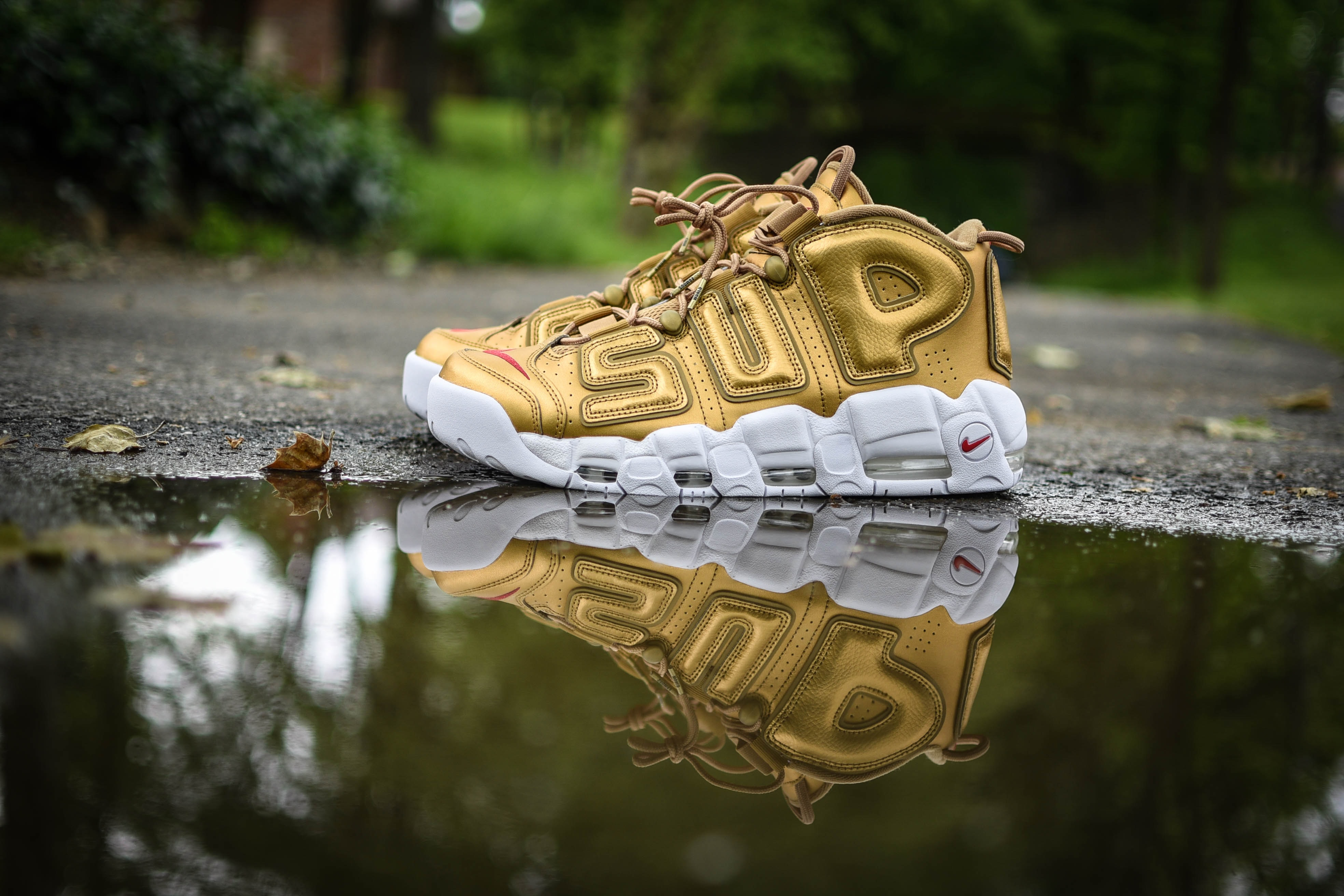 "Gold ""SUP"" Nike shoes reflect in a puddle on the road"