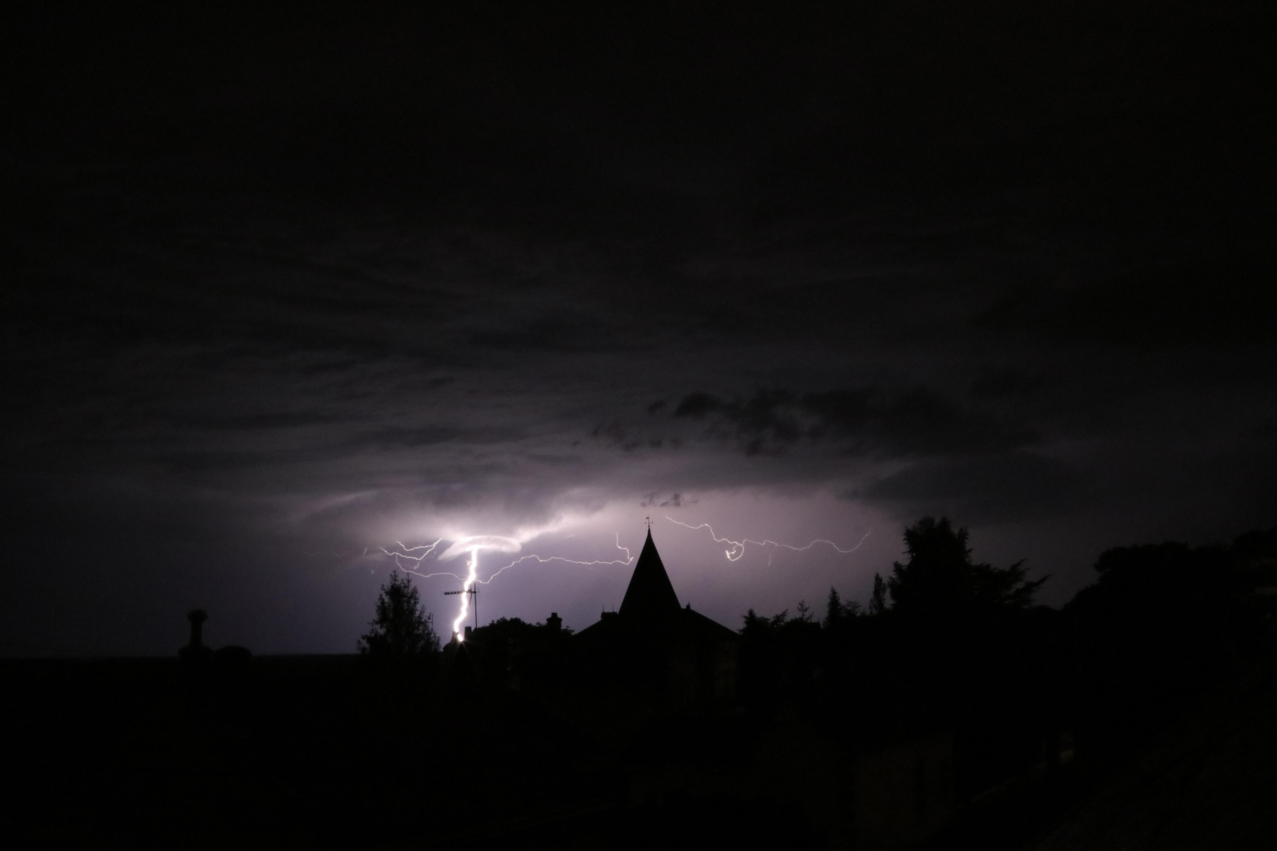 lightning strikes on land near building at night