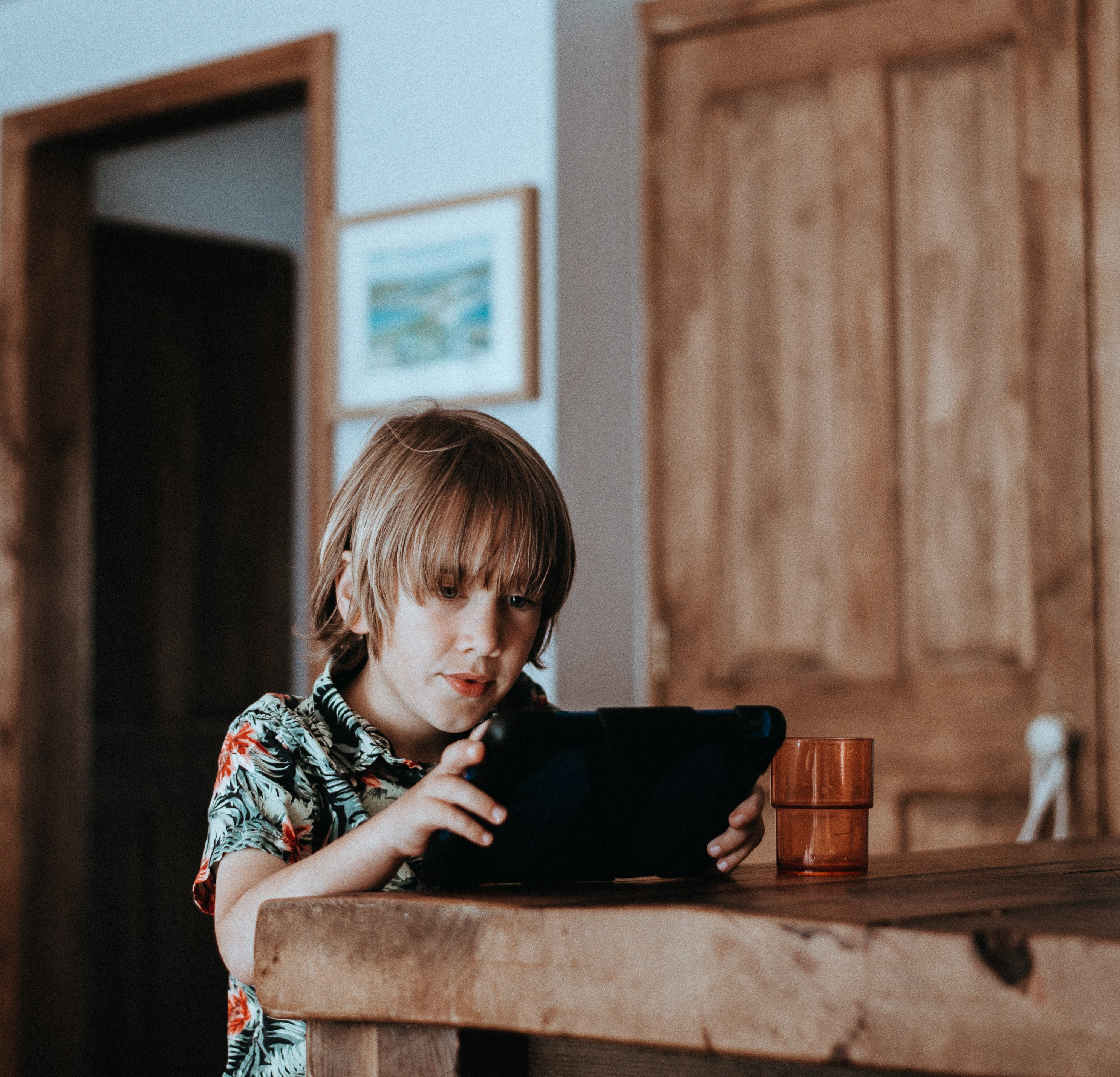A child sits at a wood table in a house, using a digital tablet