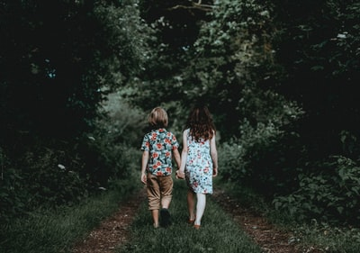 Siblings walking, holding hands