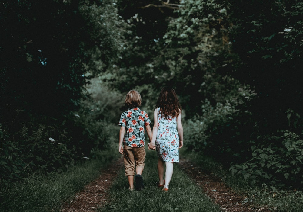 boy and girl walking hand in hand towards the woods