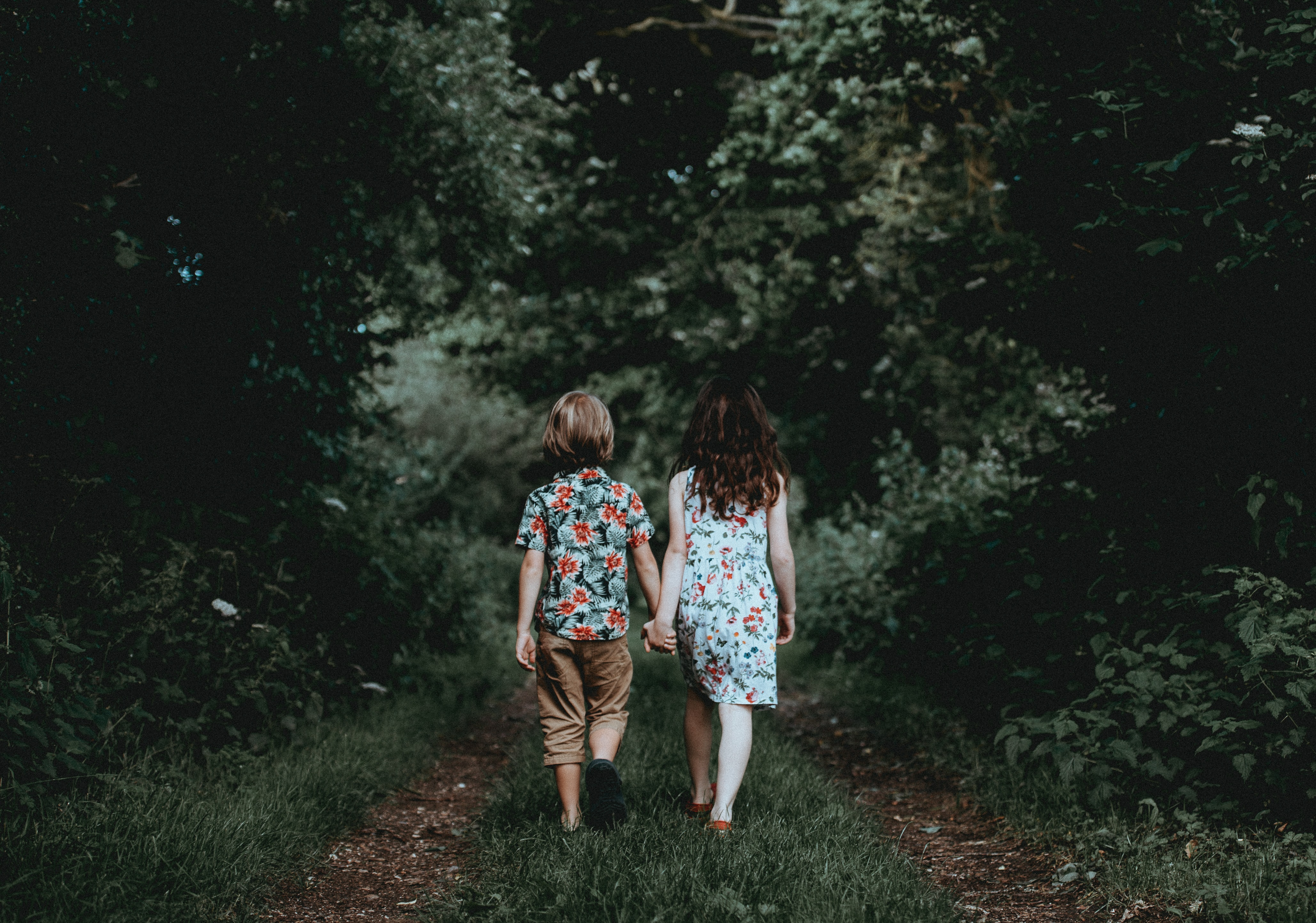 A girl and a boy hold hands and walk down a wooded trail