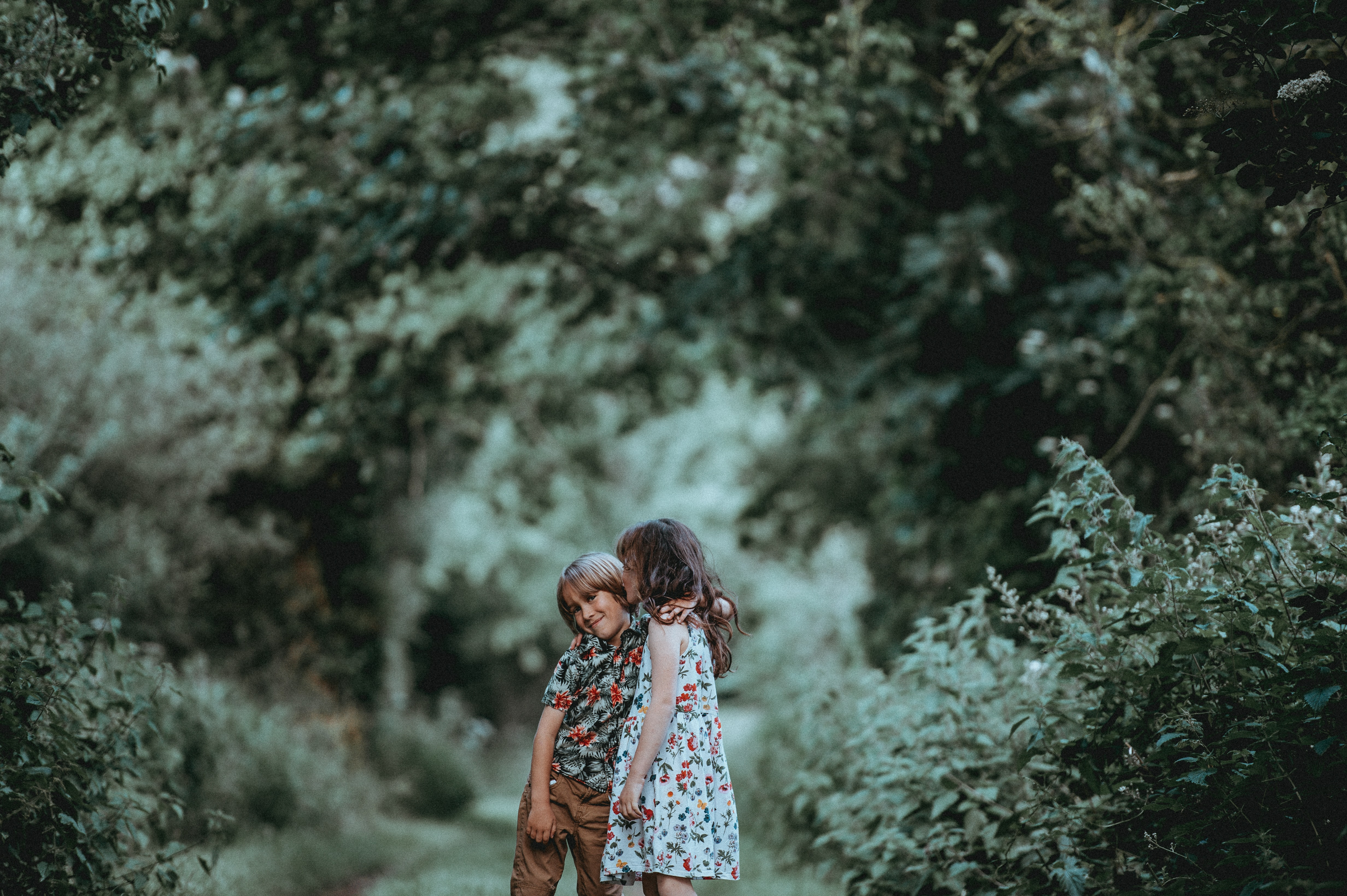 Two young children, a boy and girl, hug outdoors in a green forested area