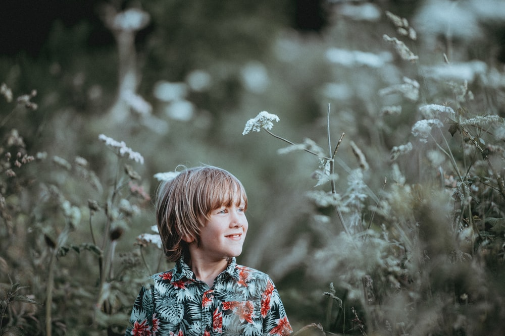 boy's red and green floral button-up collared top smiling facing grasses