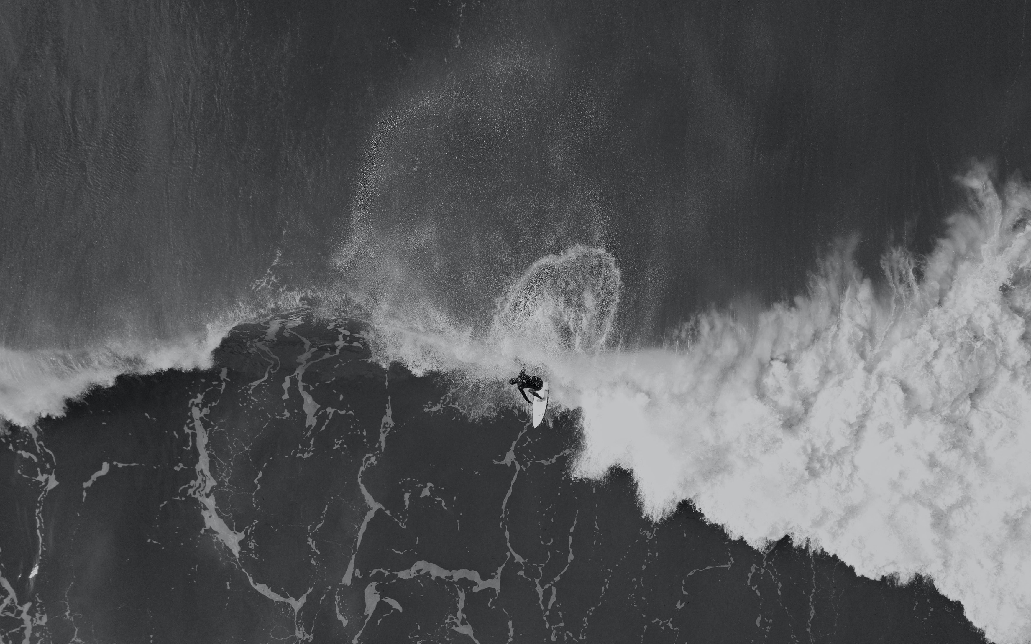 An overhead drone shot of a surfer in the foaming sea at Gisborne, New Zealand