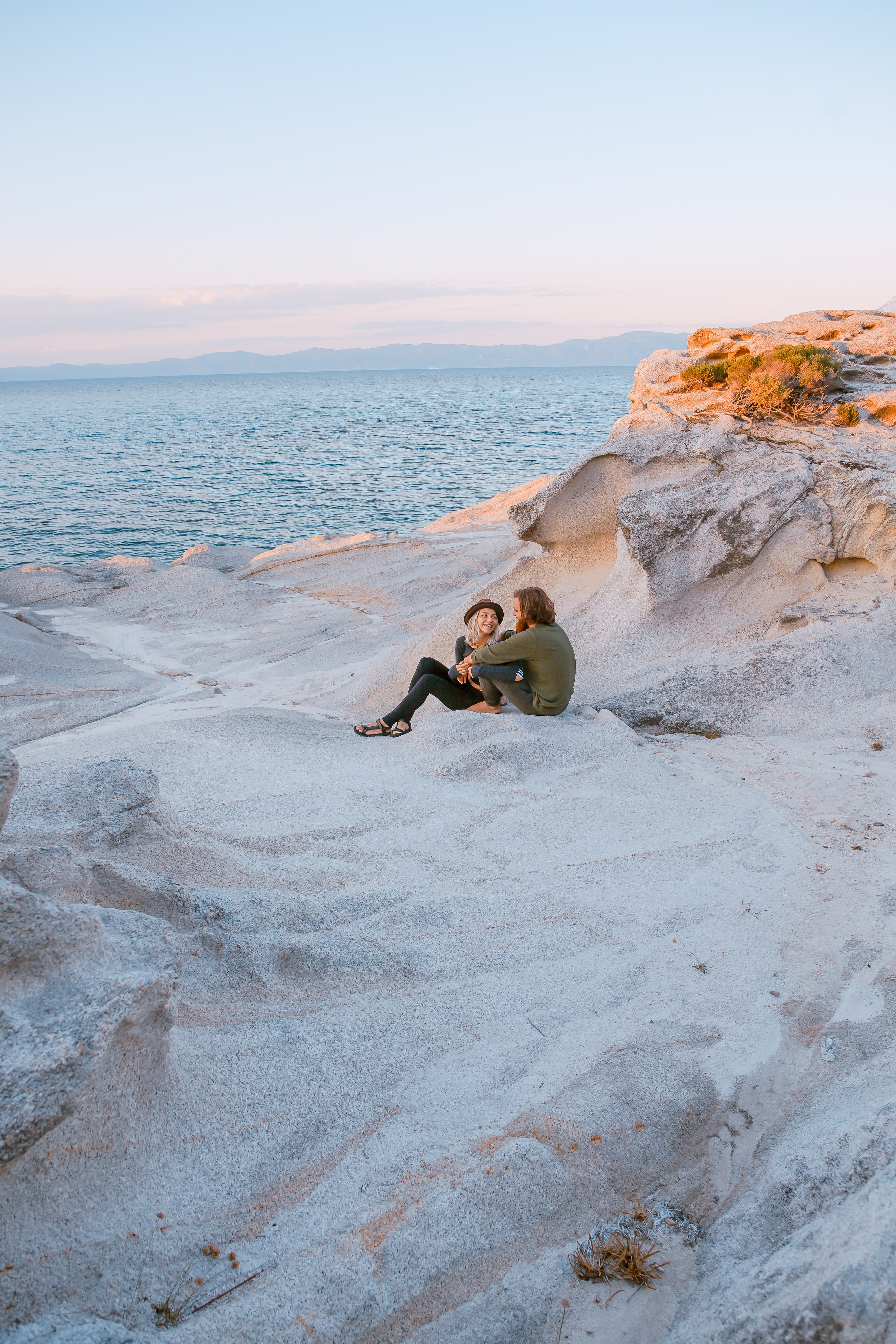 A happy couple sitting together on a white sandy beach.