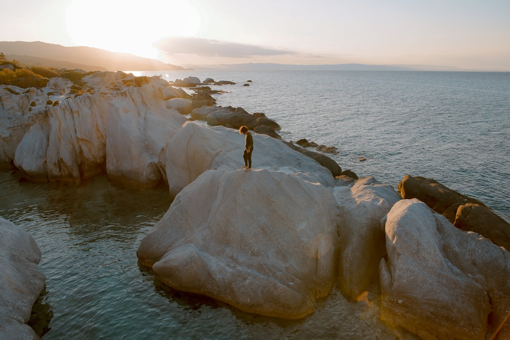 photo of person standing on brown boulder surrounded by water