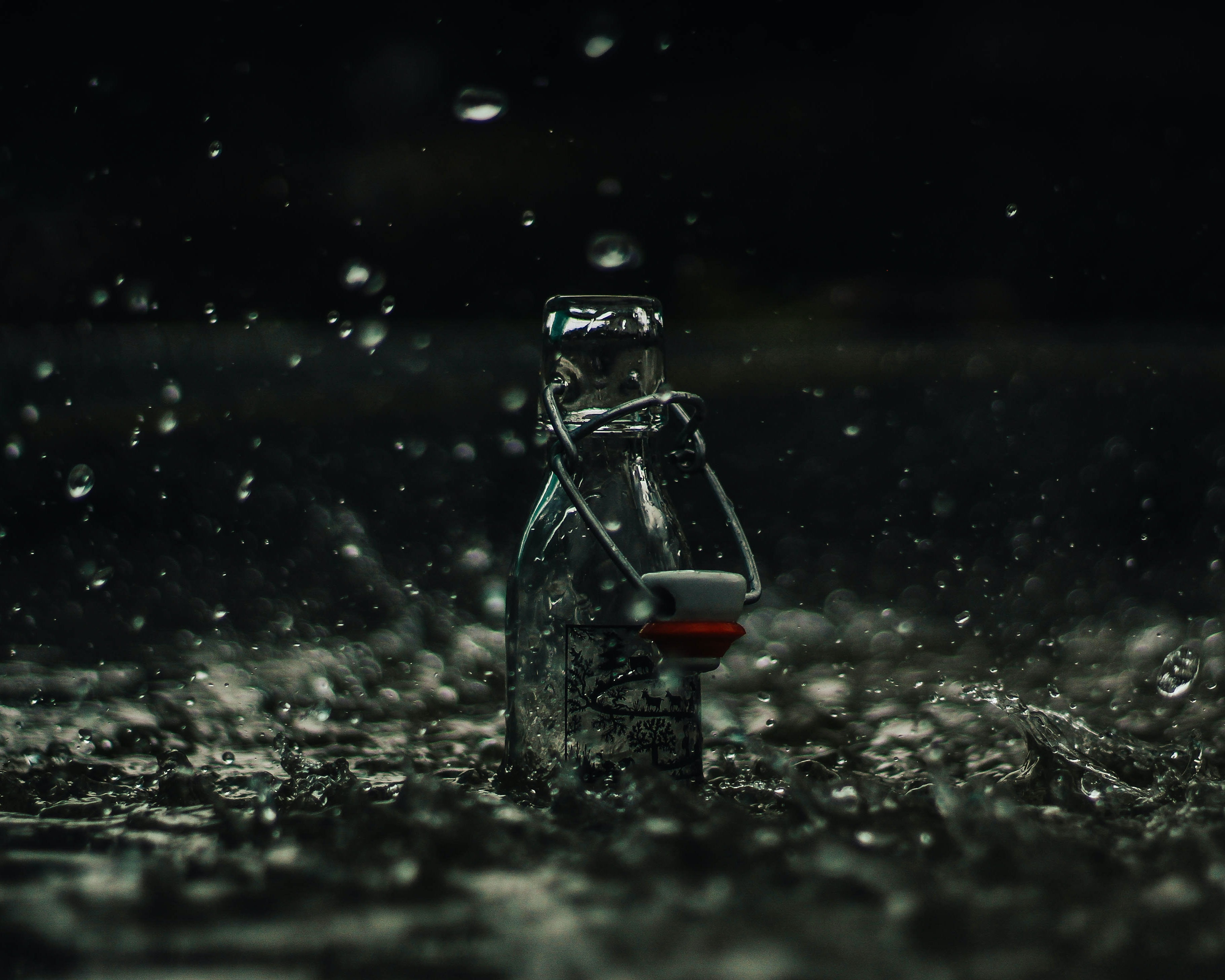 Glass bottle collects rain as water splashes around it