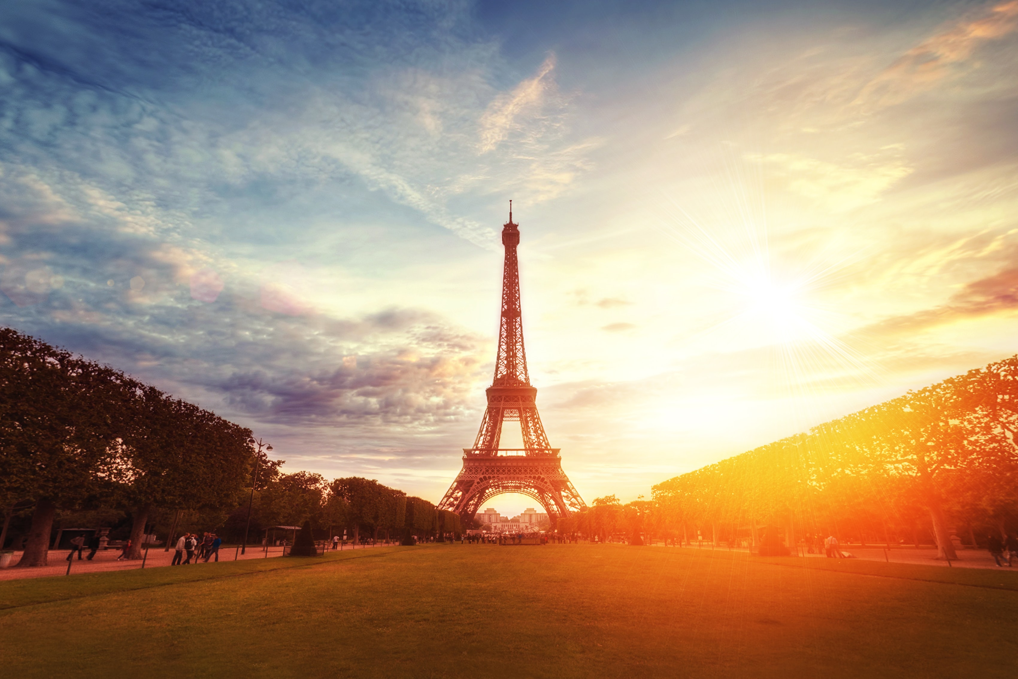 The Eiffell Tower with a blue sky, light clouds, and golden sunset with lens flare.