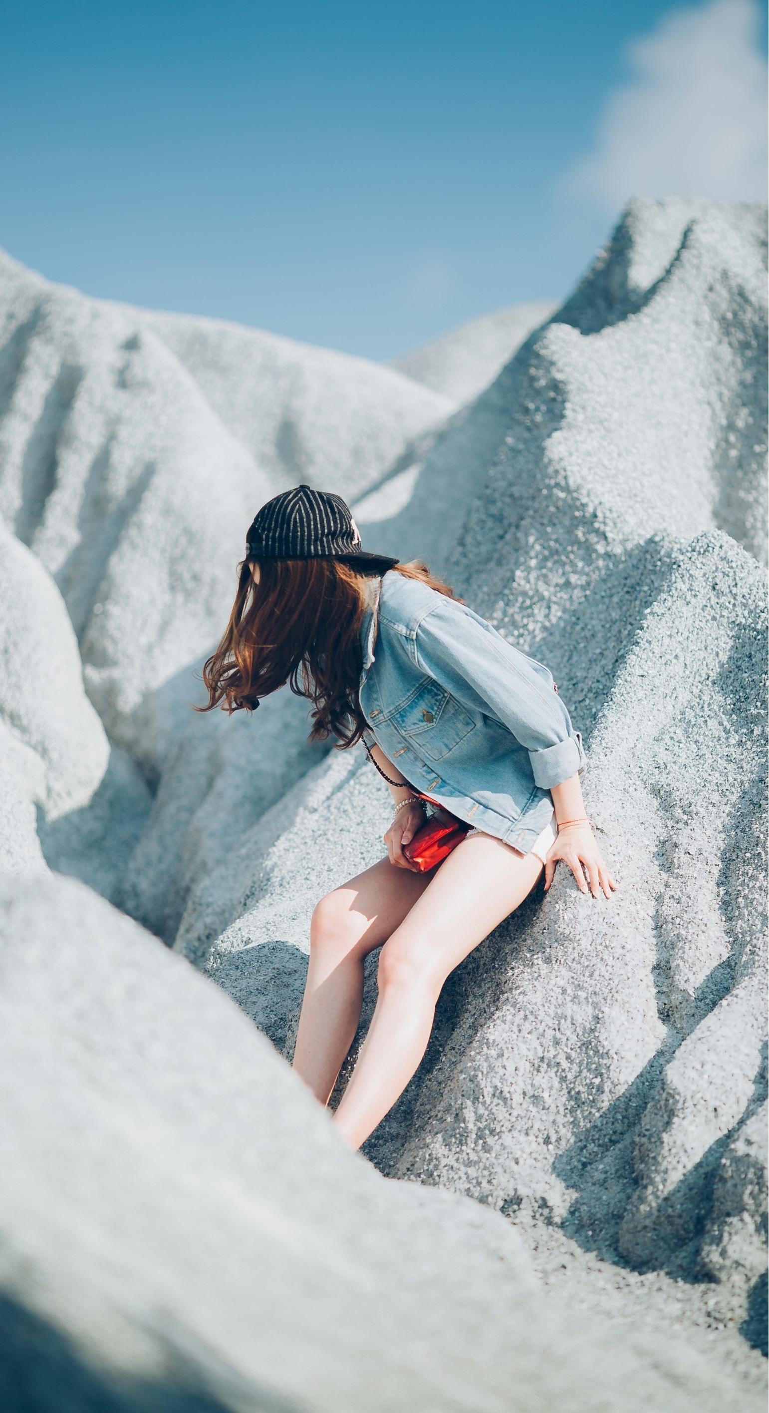 A woman in a baseball cap and denim shirt leans against sand dunes in Thailand