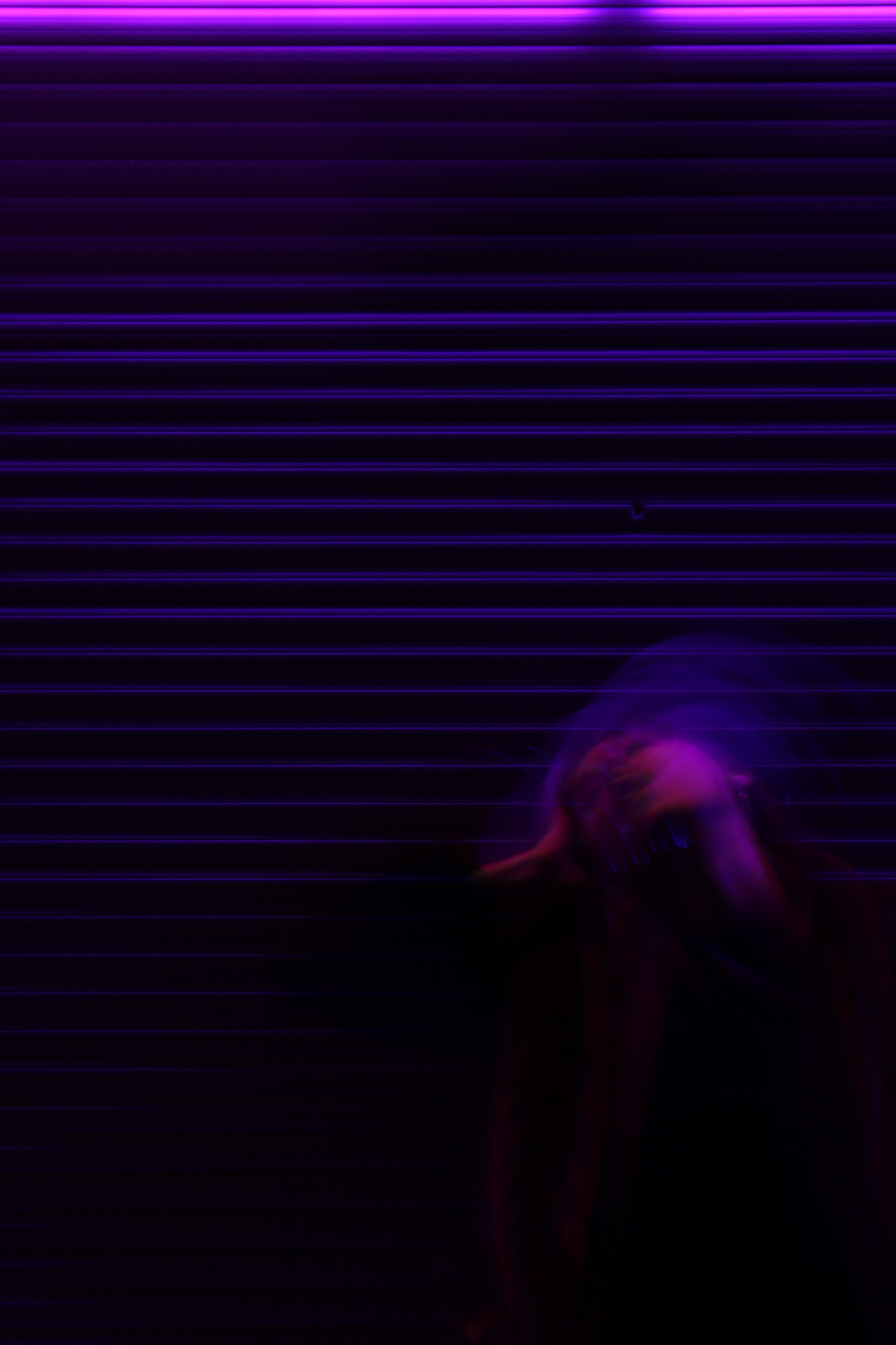 A freaky shot of a woman tilting her head back, standing in front of a garage door at night.