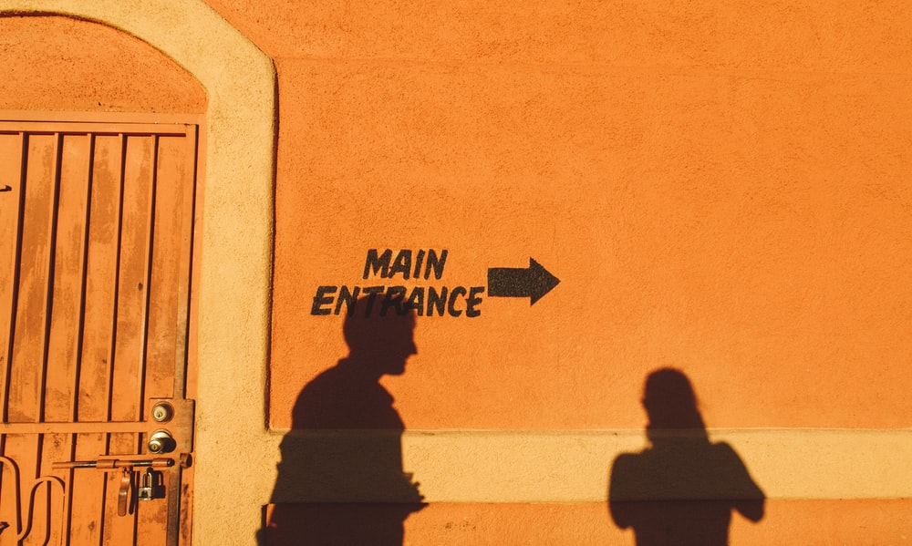 silhouette photo of two person reflecting on orange painted wall with main entrance print