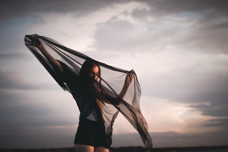 woman holding black silk garment during daytime