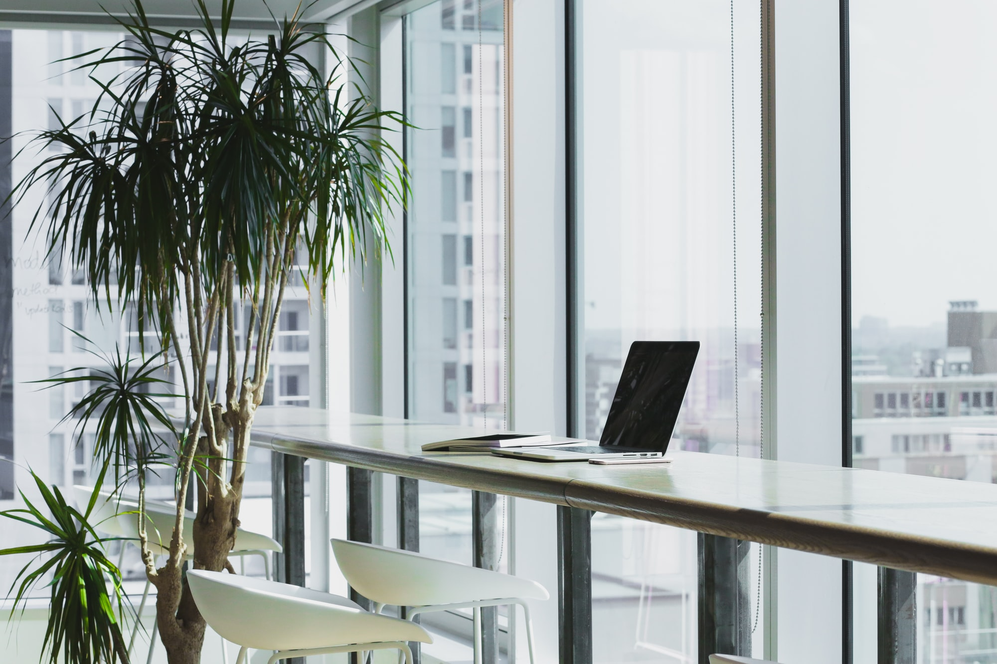 Stock image of a laptop sitting on a bench in a corporate office overlooking a city