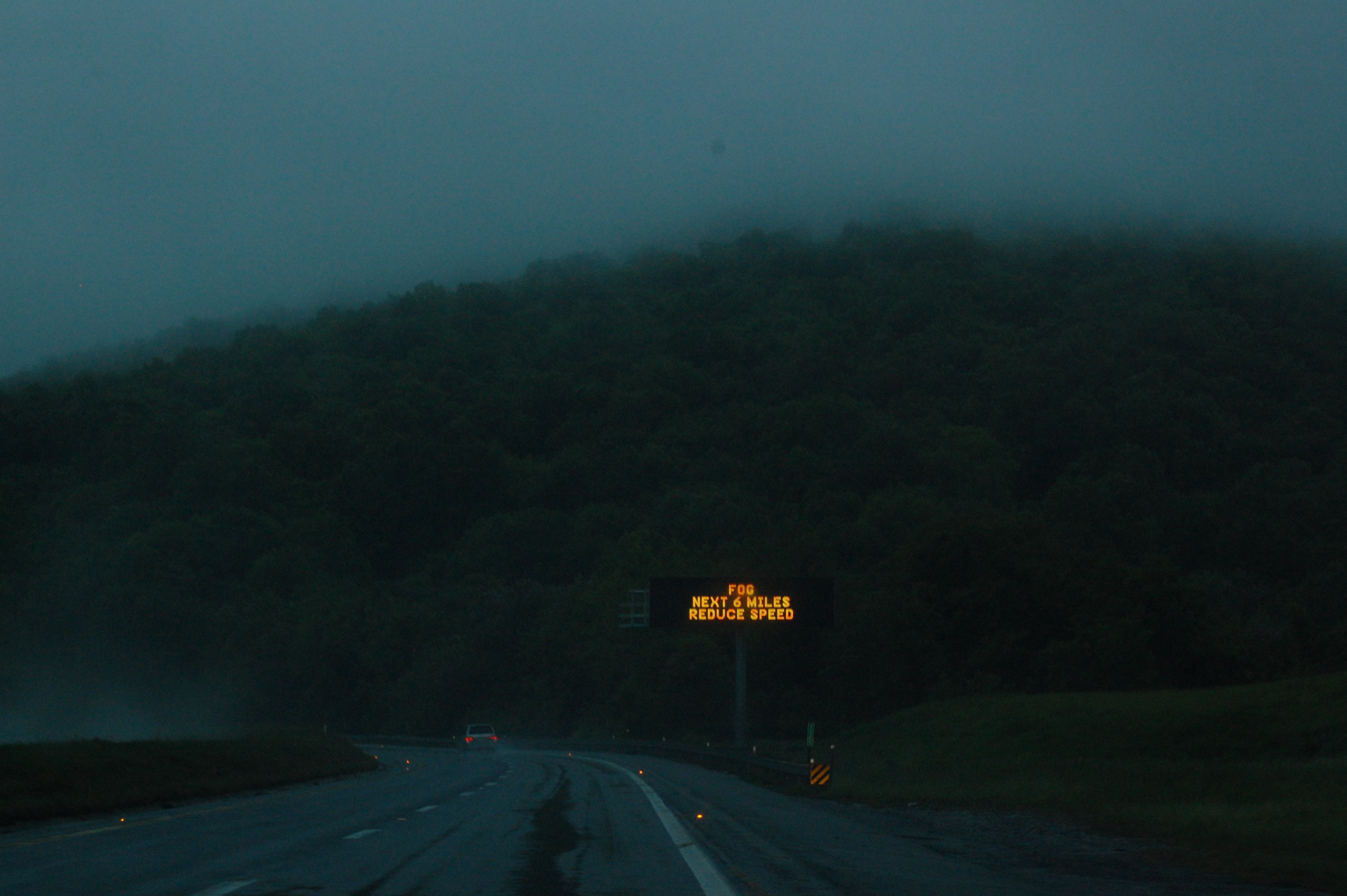 Highway sign warns drivers of fog on the road at night