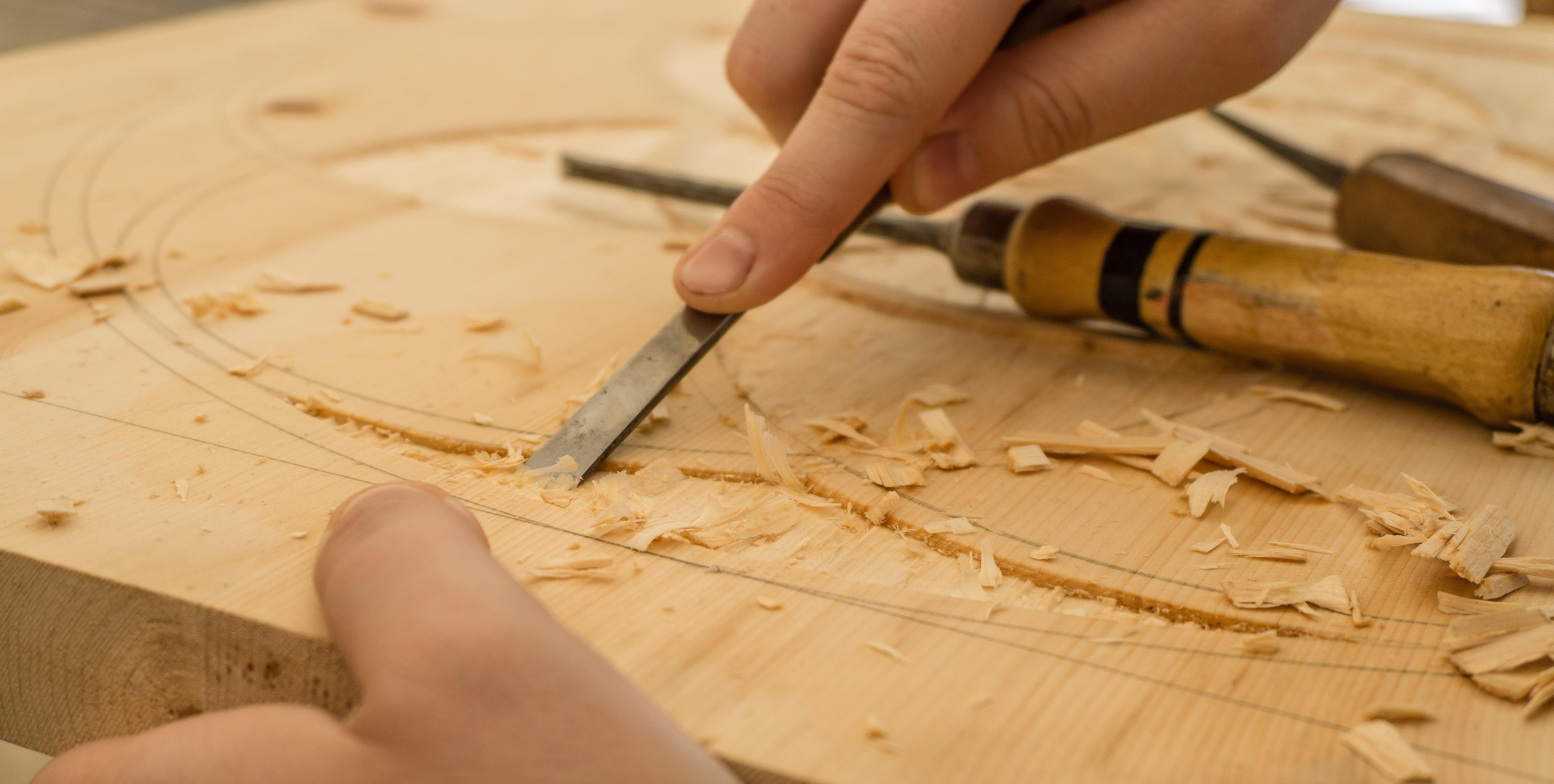 Close-up of a person using a chisel to carve in a large wooden board