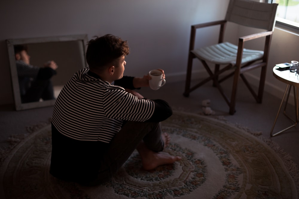 man sitting on rug in front of window