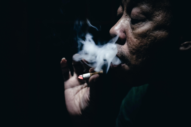 Dark skinned old man smoking a cigarette in the dark.