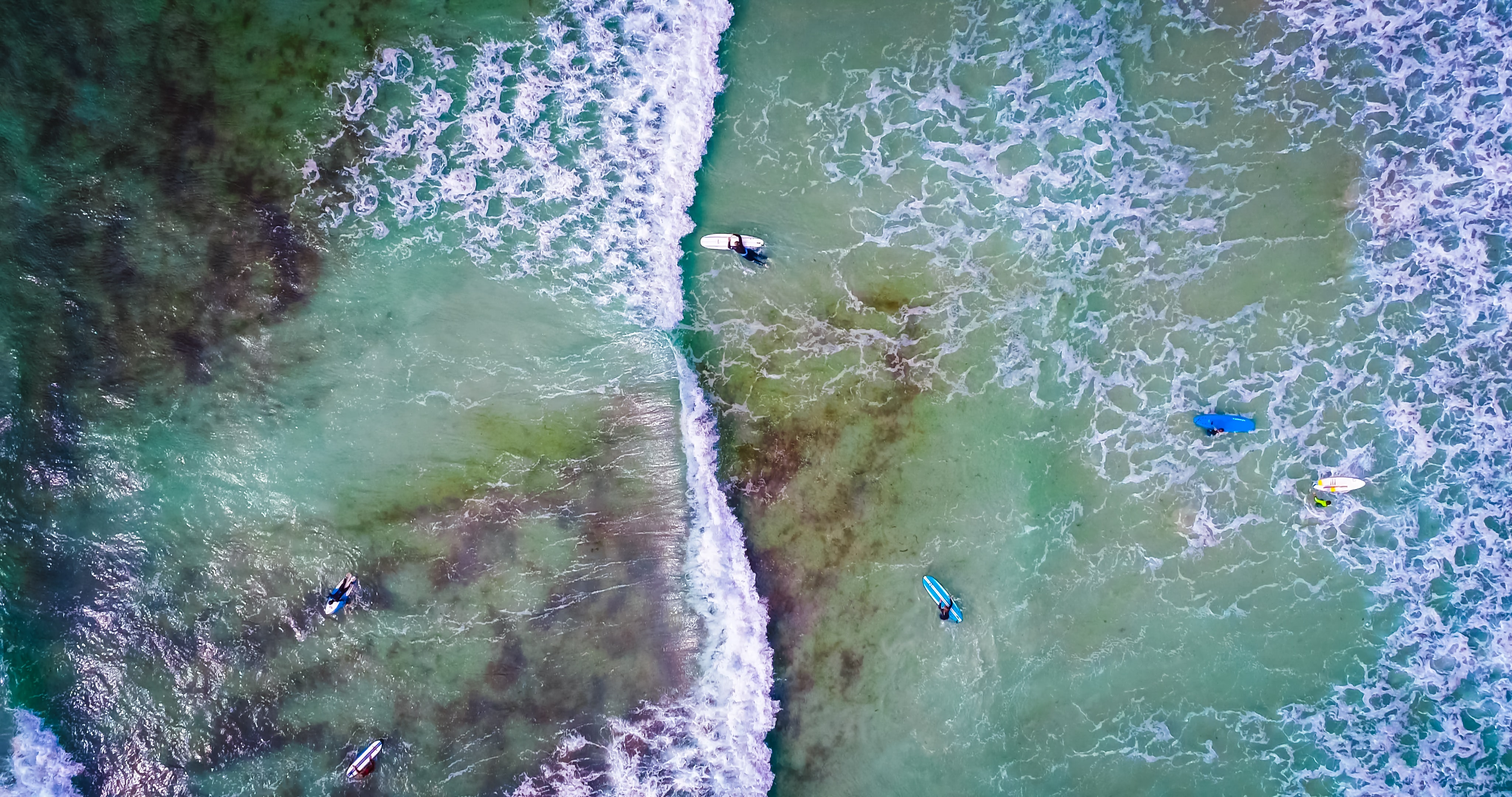 An aerial drone overhead shot of surfers in the sea at Guernsey Surf School, with crystal clear waters beneath