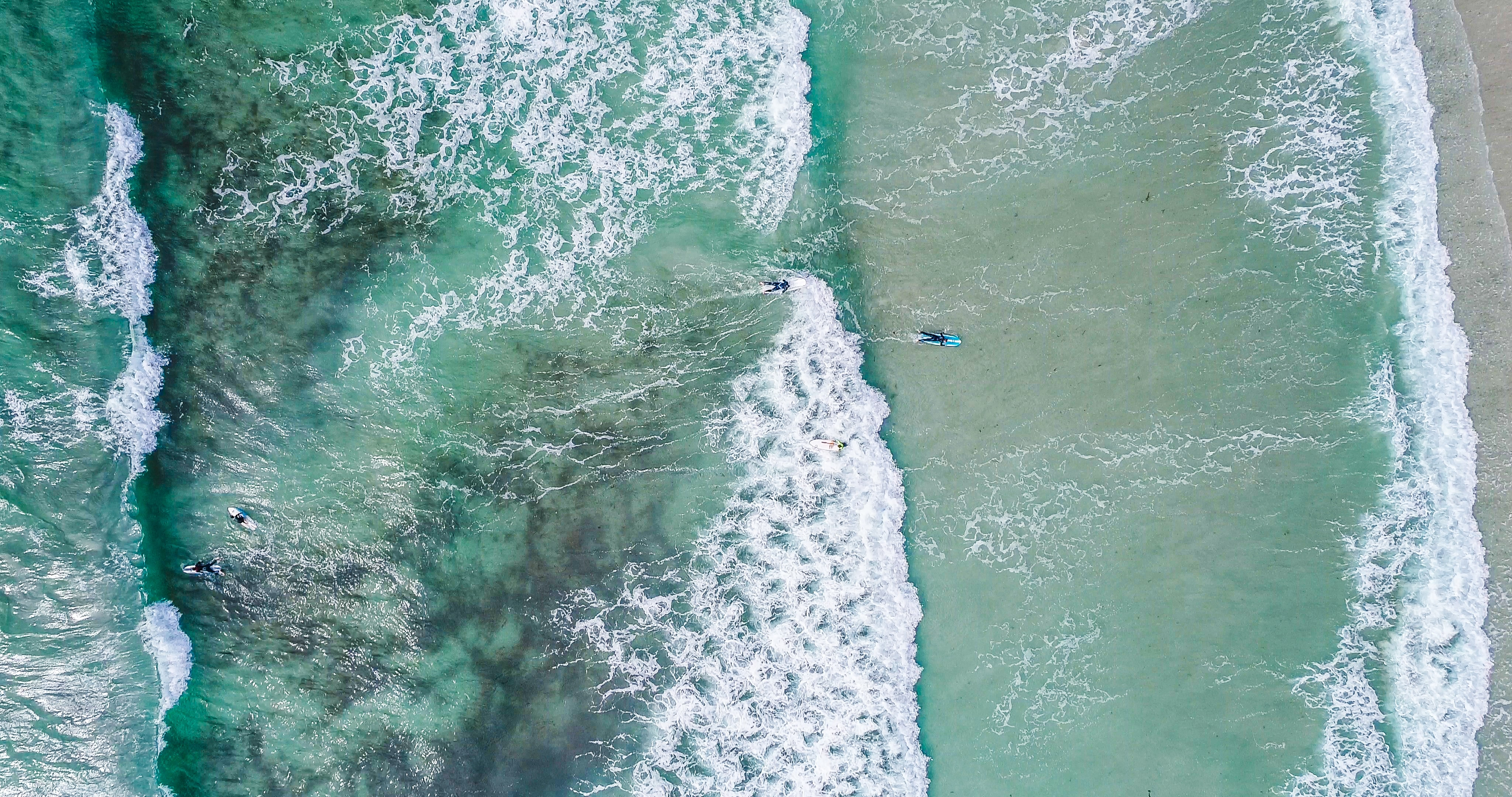 Drone aerial view of surfers in the ocean at Guernsey Surf School