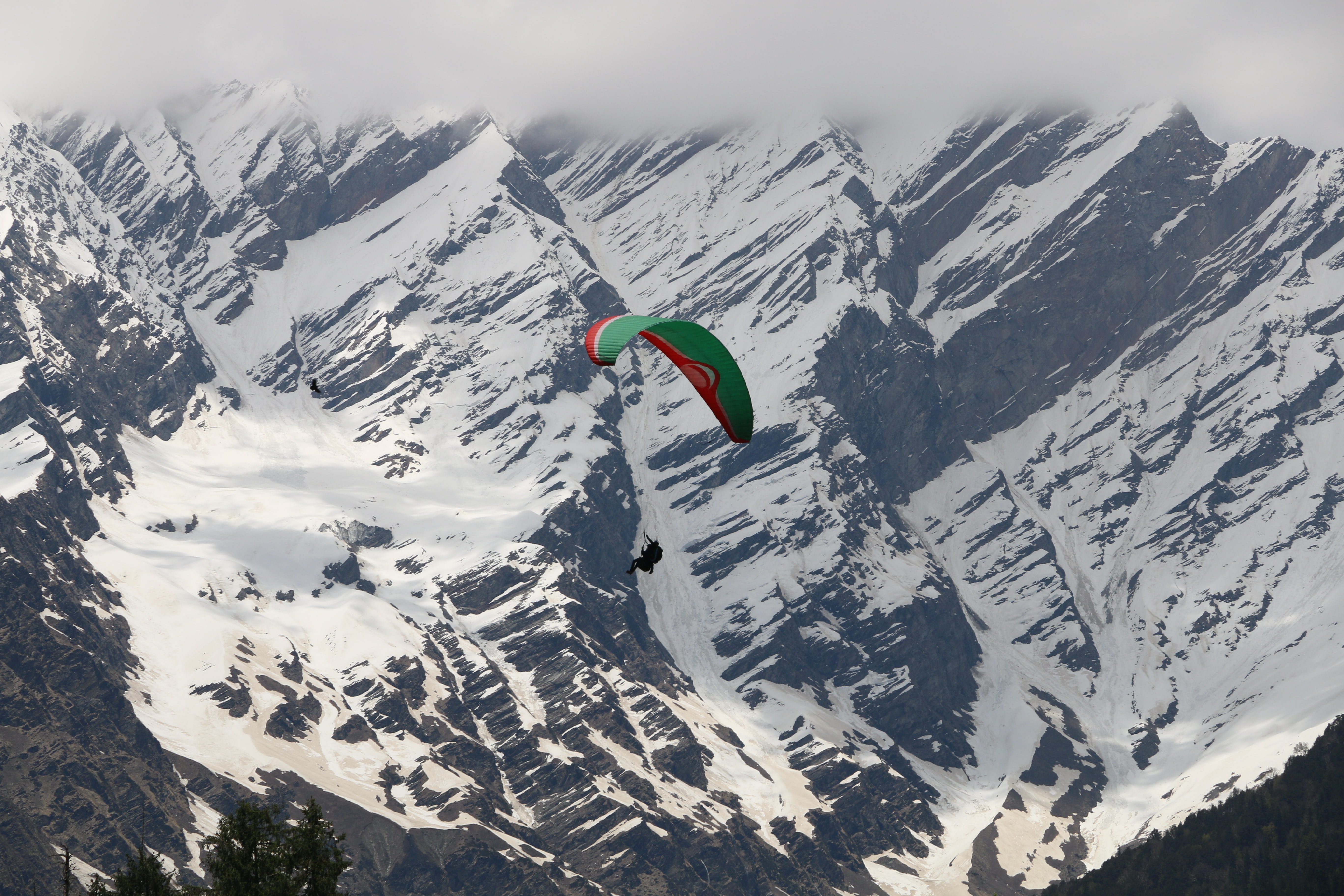 Extreme sports fanatic parachutes over a snowy mountain landscape