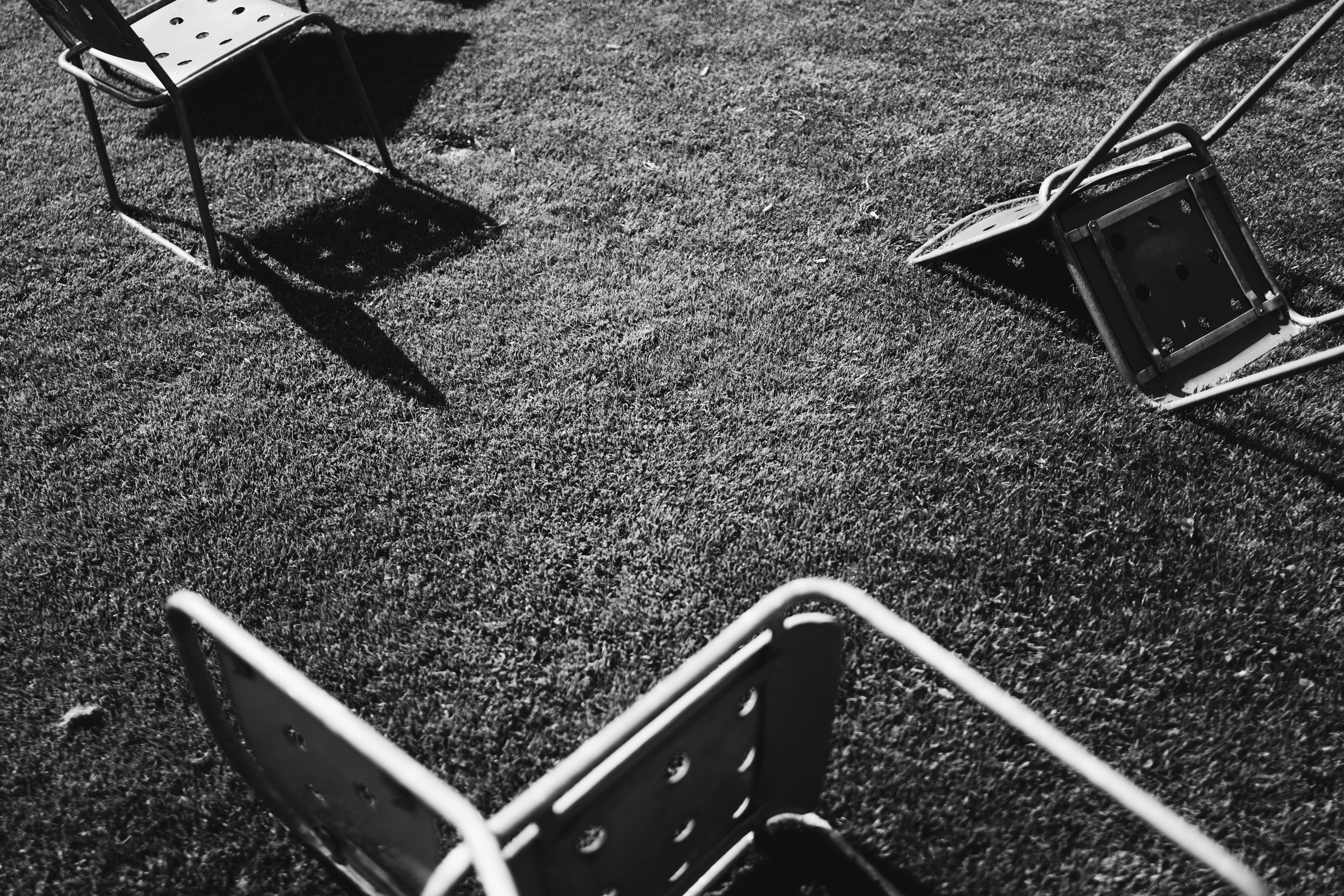 Black and white photo of fallen chairs on grass with shadow